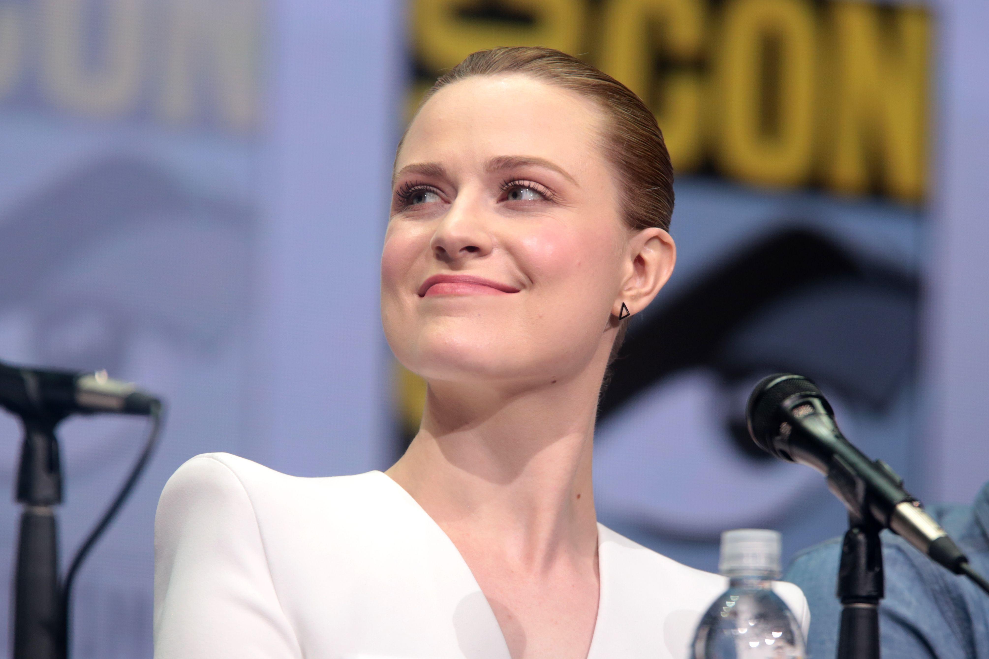 Evan Rachel Wood in white outfit, looking smug.