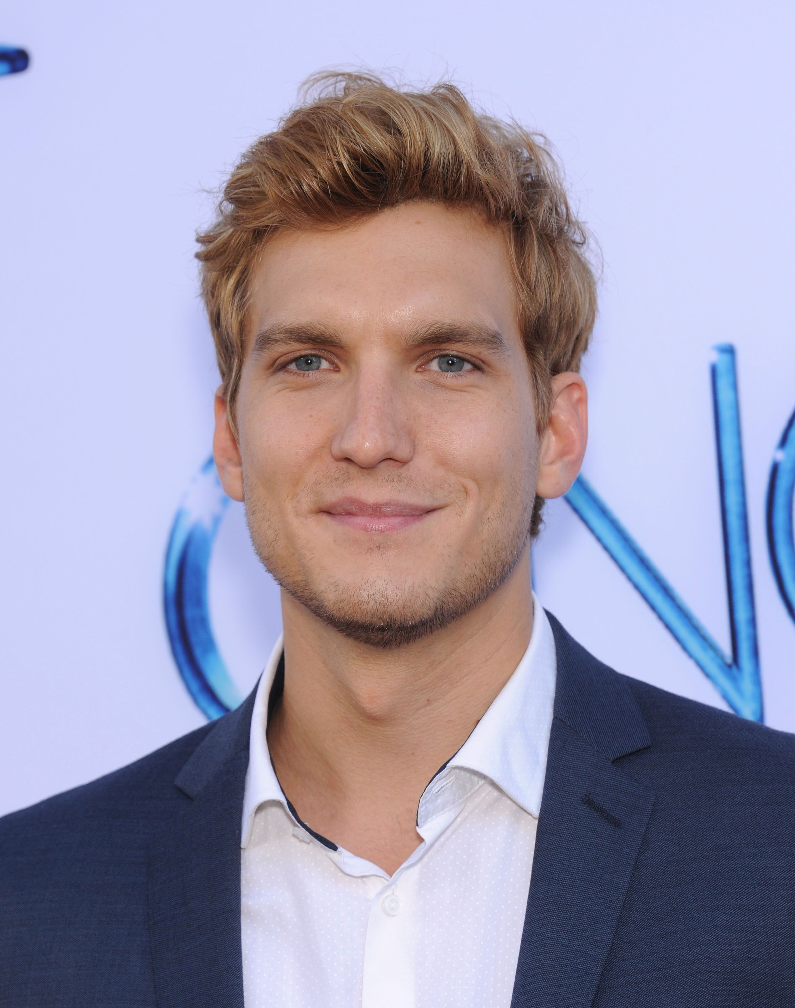 Close-up of Scott Michael Foster wearing a blue jacket and white shirt.