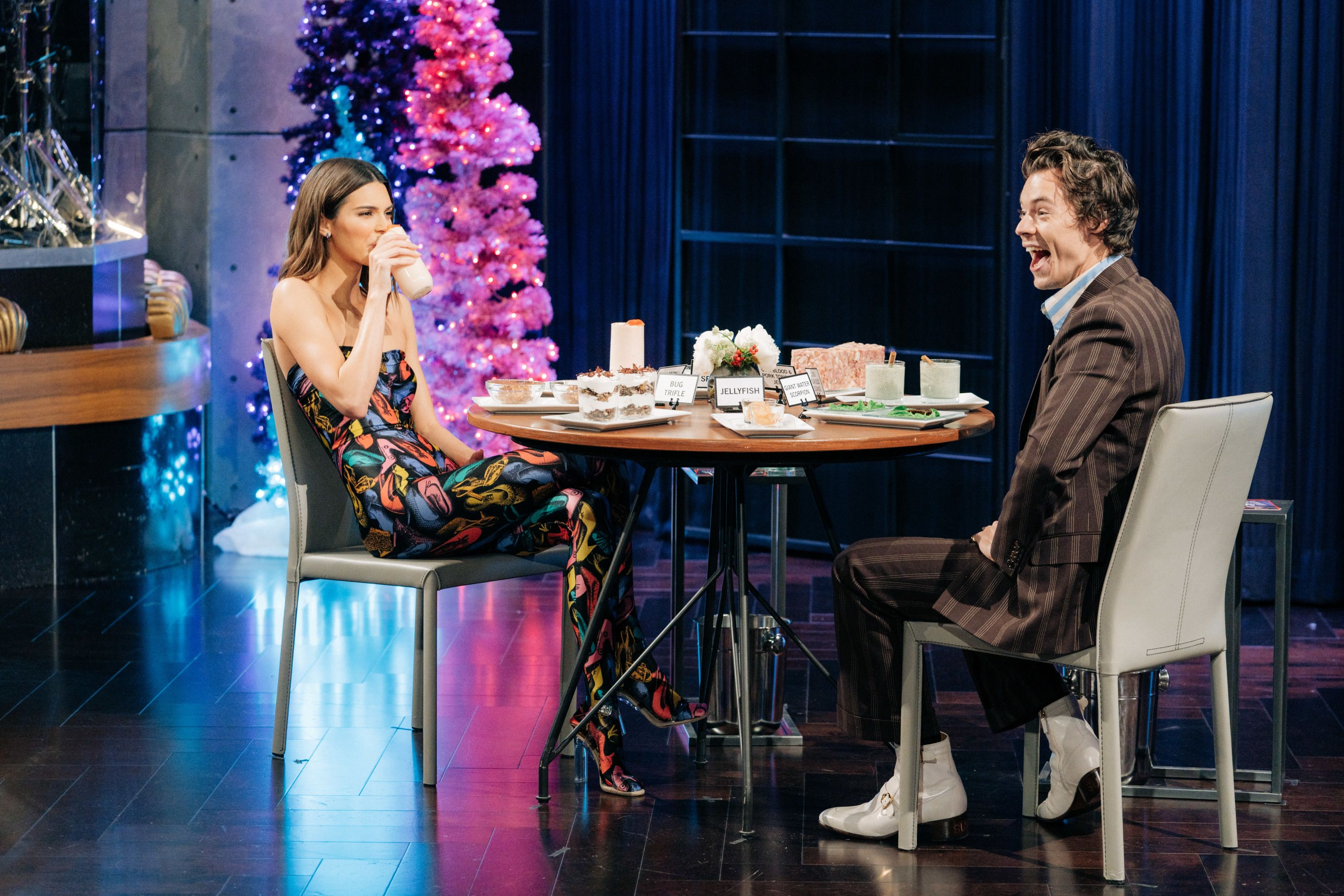 Kendall Jenner (left) and Harry Styles (right) sit at a table eating an array of food