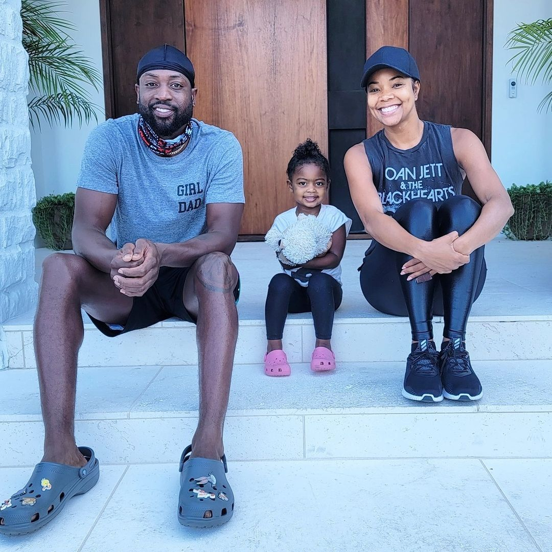 Gabrielle Union, Dwayne Wade, and their daughter, sit on the front steps of their home, dressed in workout gear.