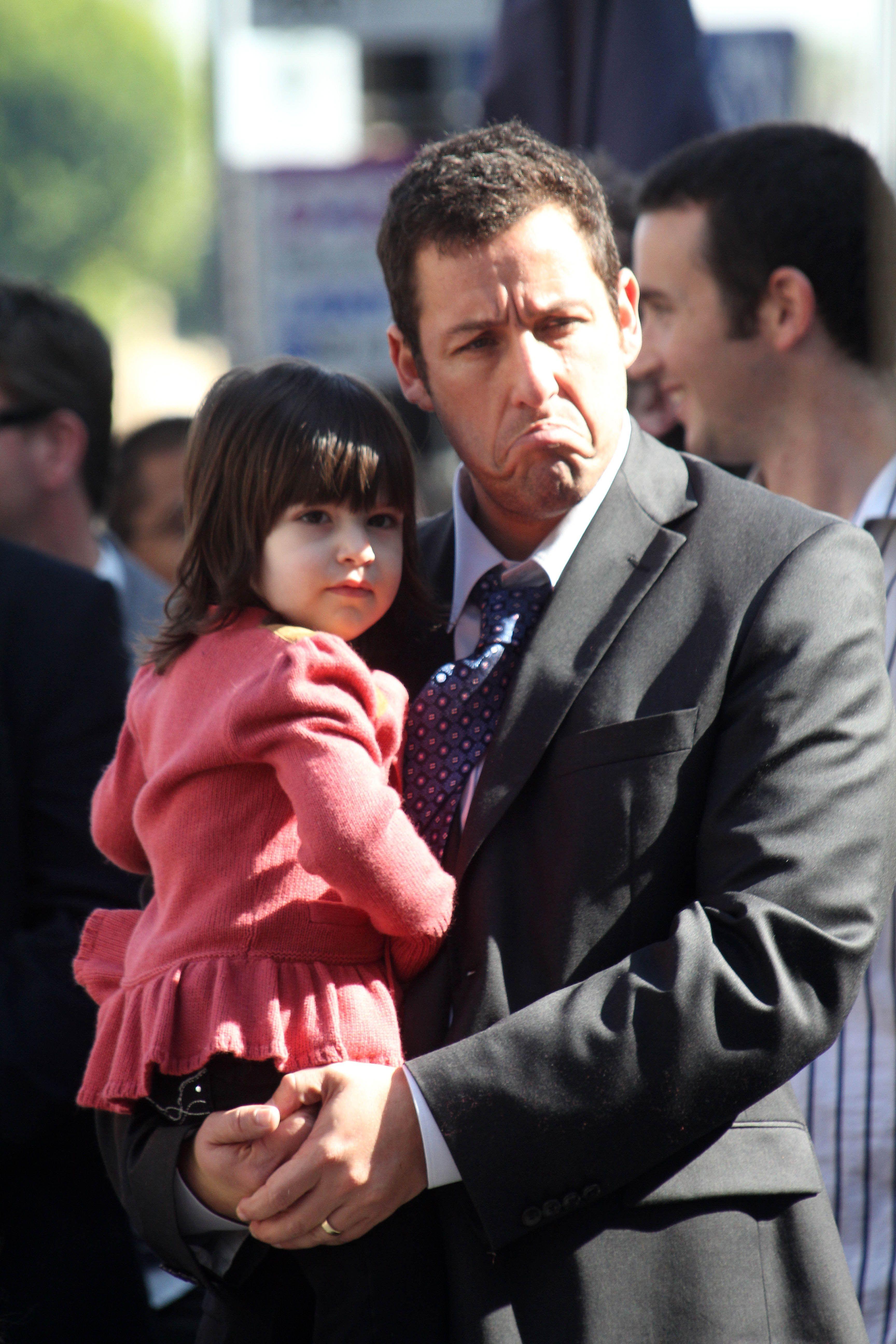 Adam Sandler hold Sunny Sandler.
