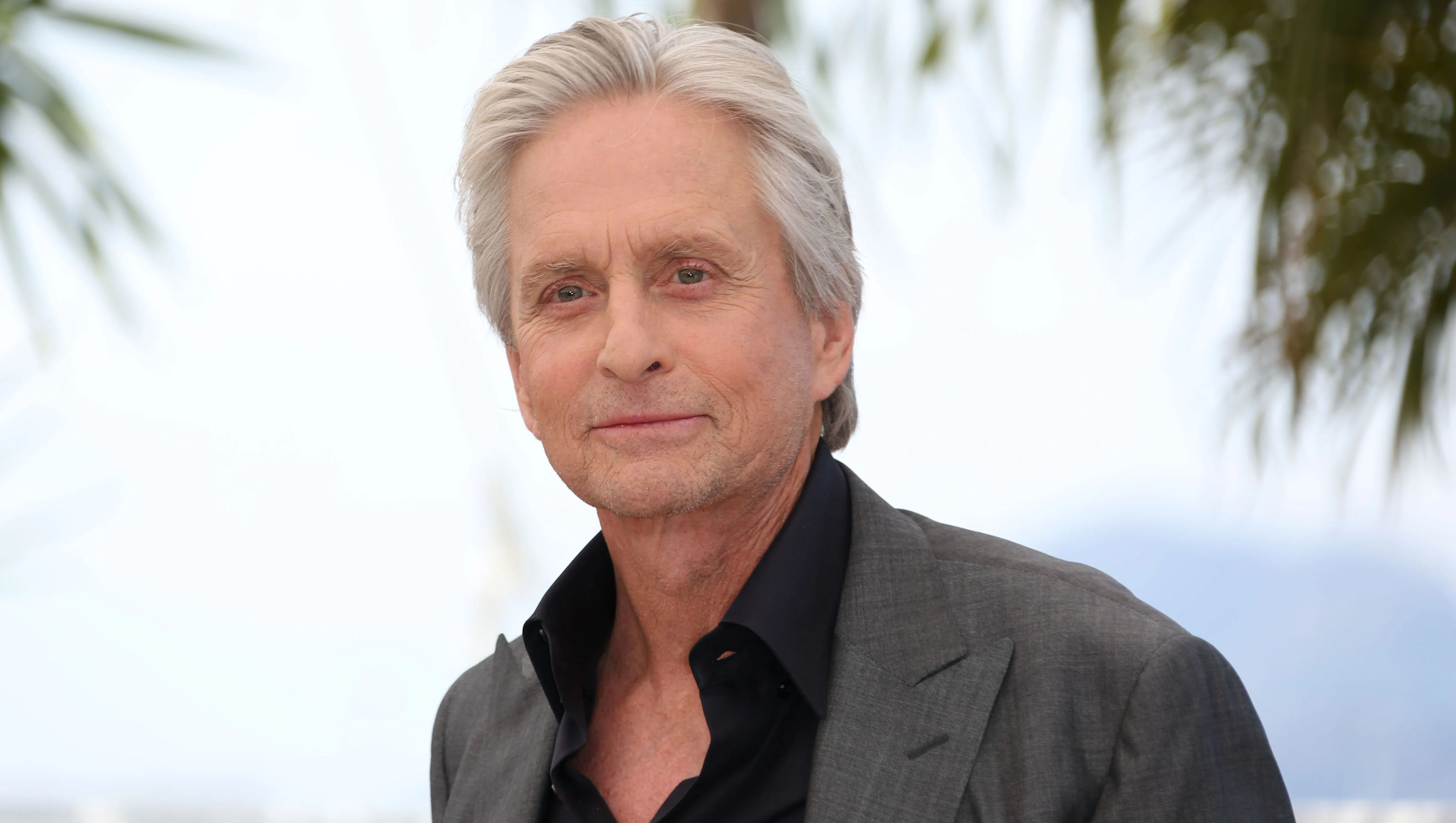 Michael Douglas in a black button up and gray sport coat