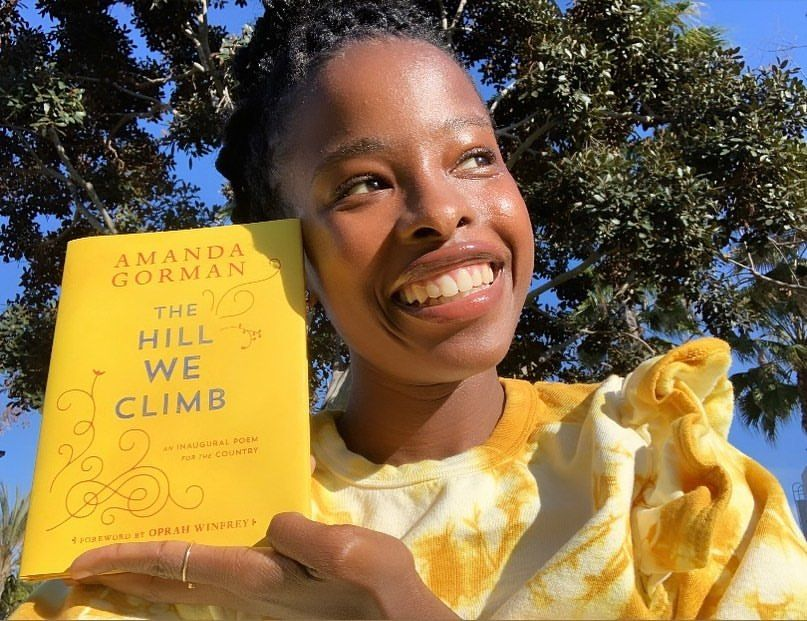 A photo showing Amanda Gorman posing in a yellow sweater, with her book titled 'The Hill We Climb'