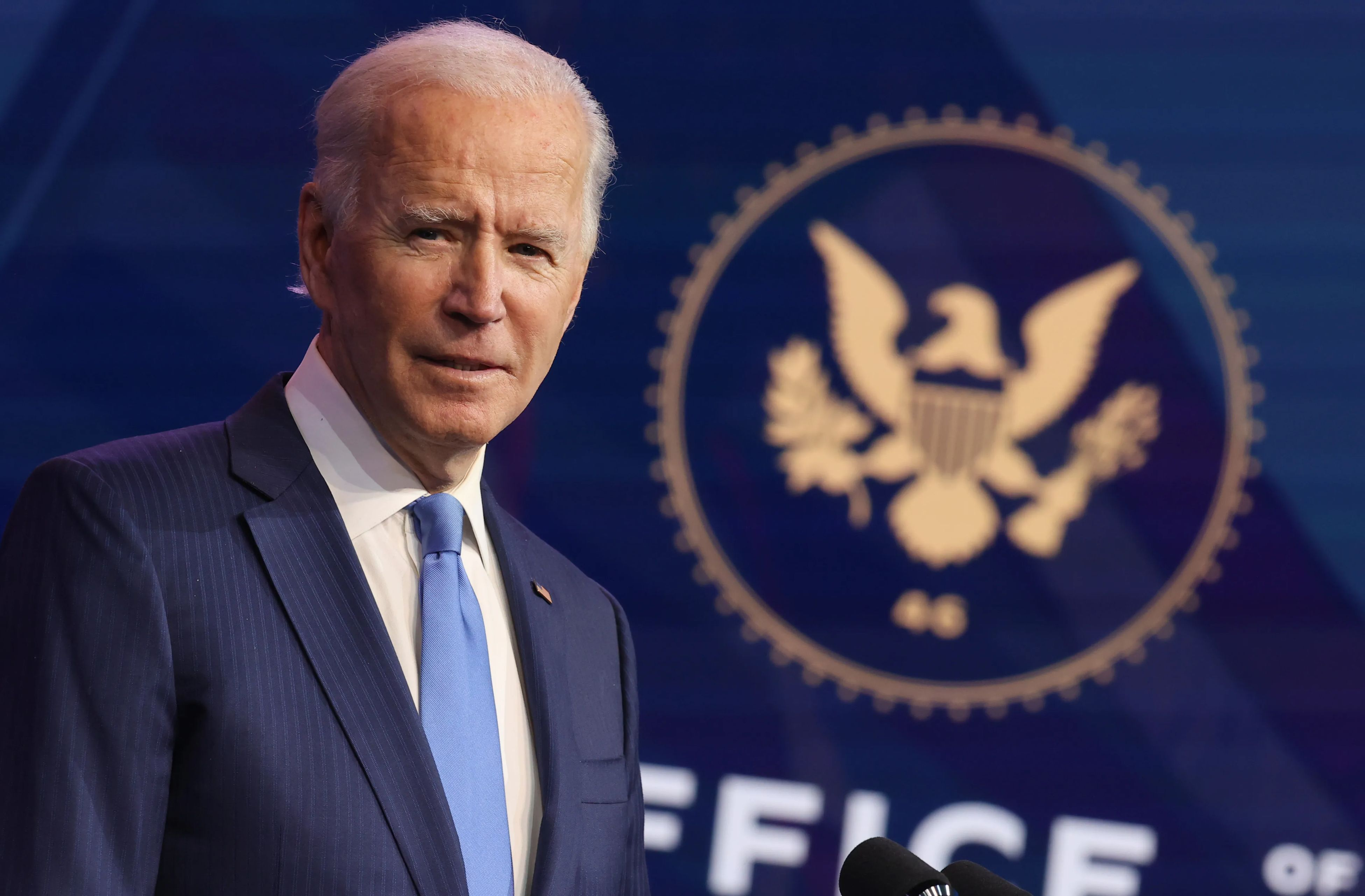 President Joe Biden in front of the Seal of the President of the United States.