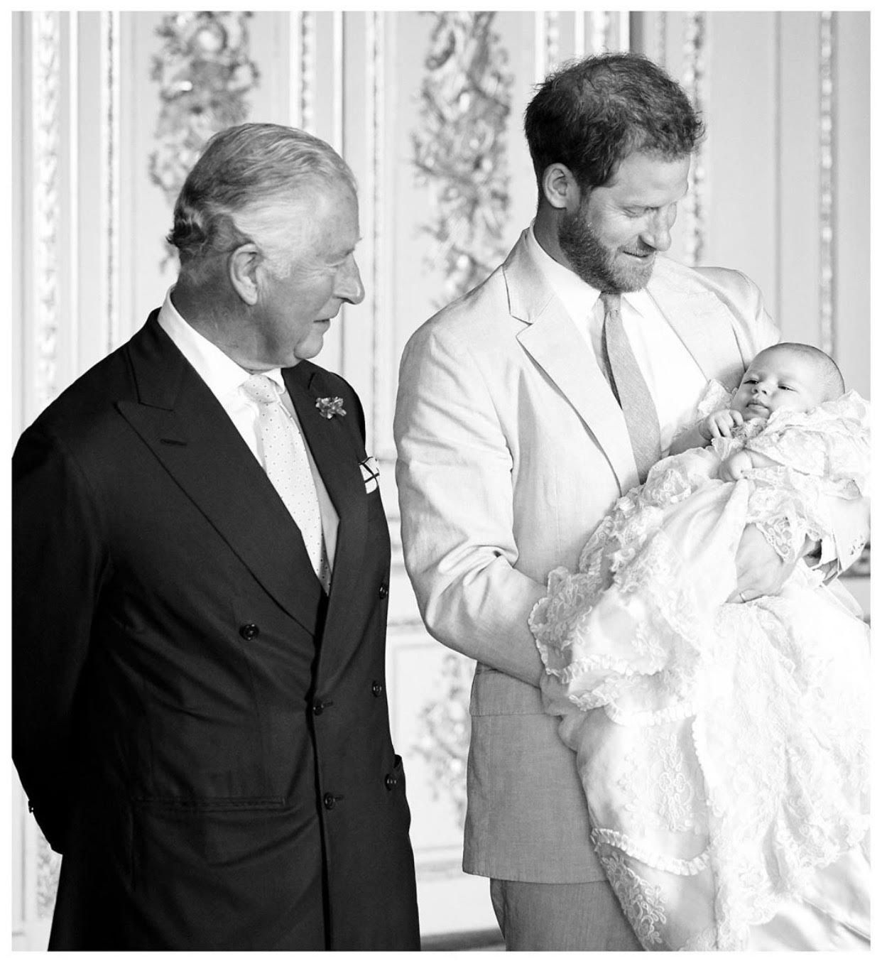 Prince Charles standing next to his son Prince Harry holding his son Archie