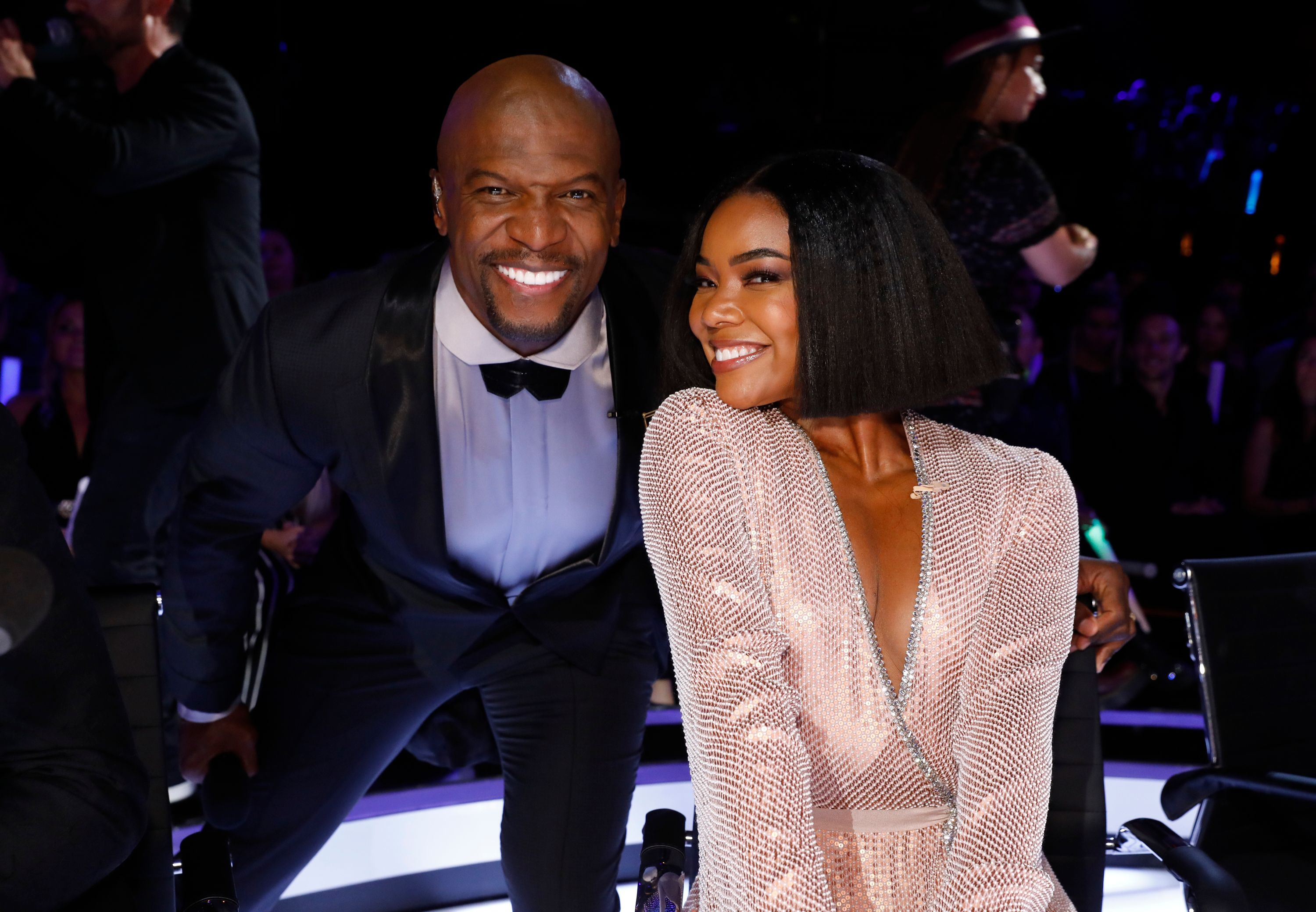 Terry Crews (left) poses with his arm around Gabrielle Union's (right) chair