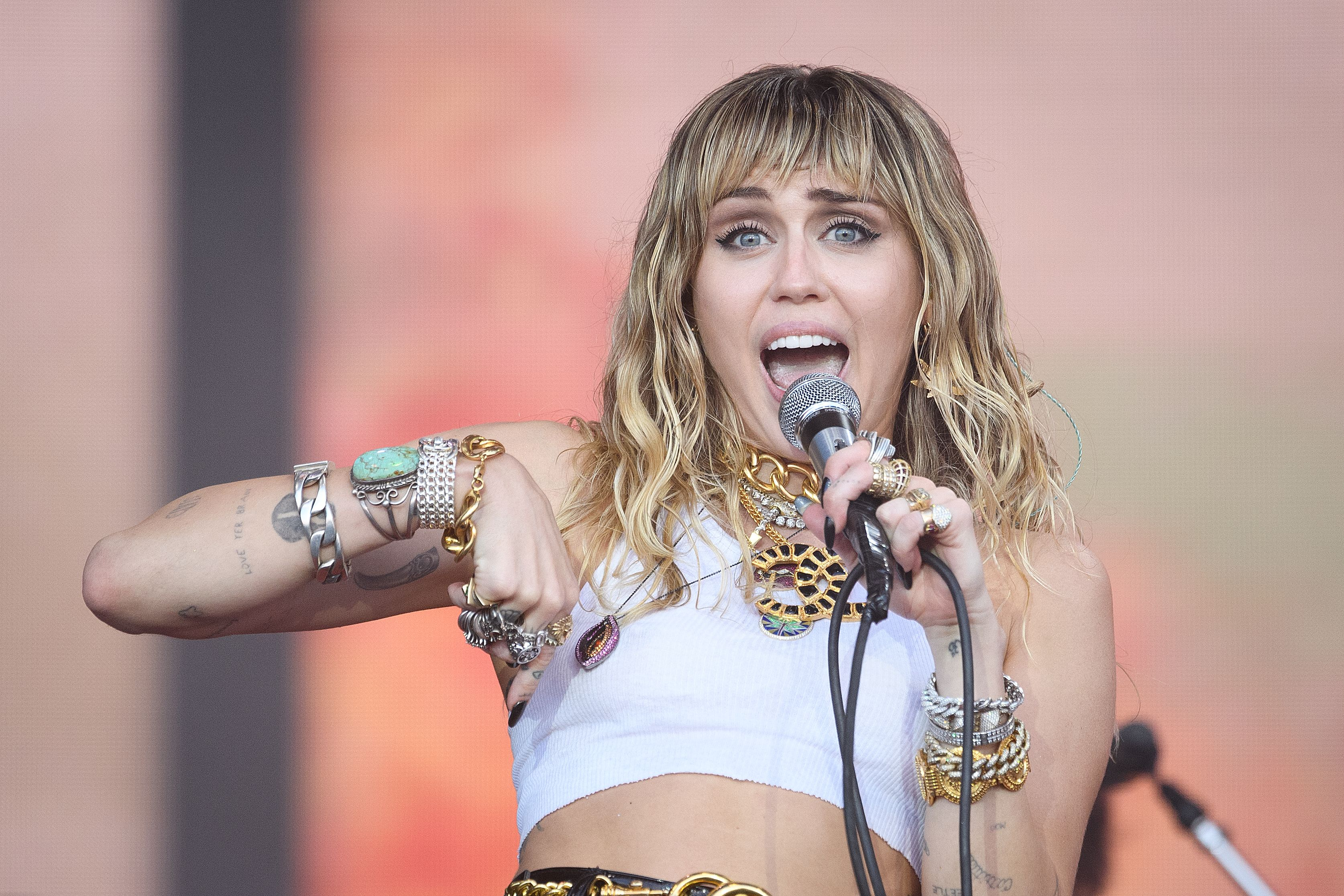 Miley Cyrus sings to a crowd, holding a microphone