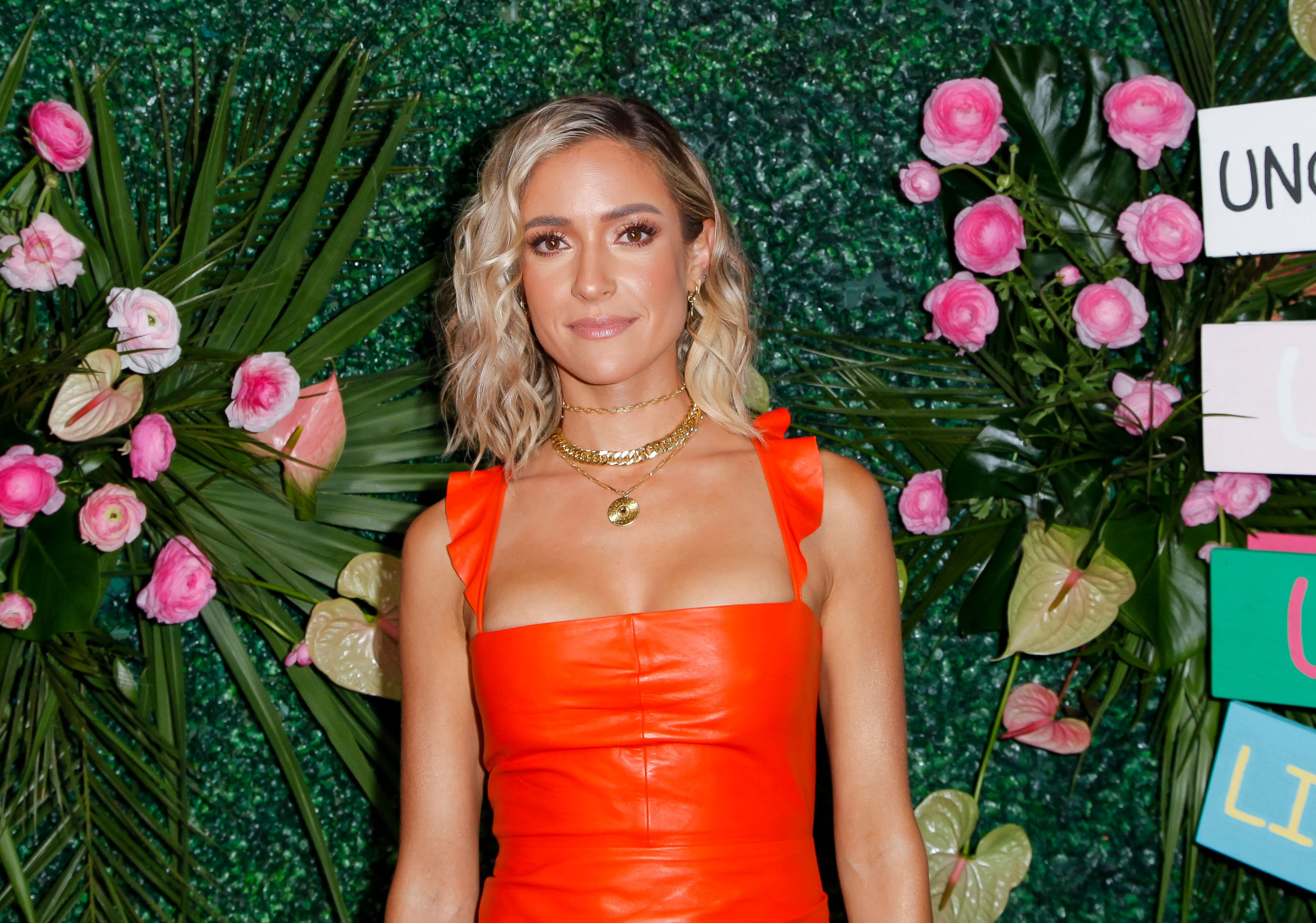 Kristin Cavallari poses in front of a grass wall