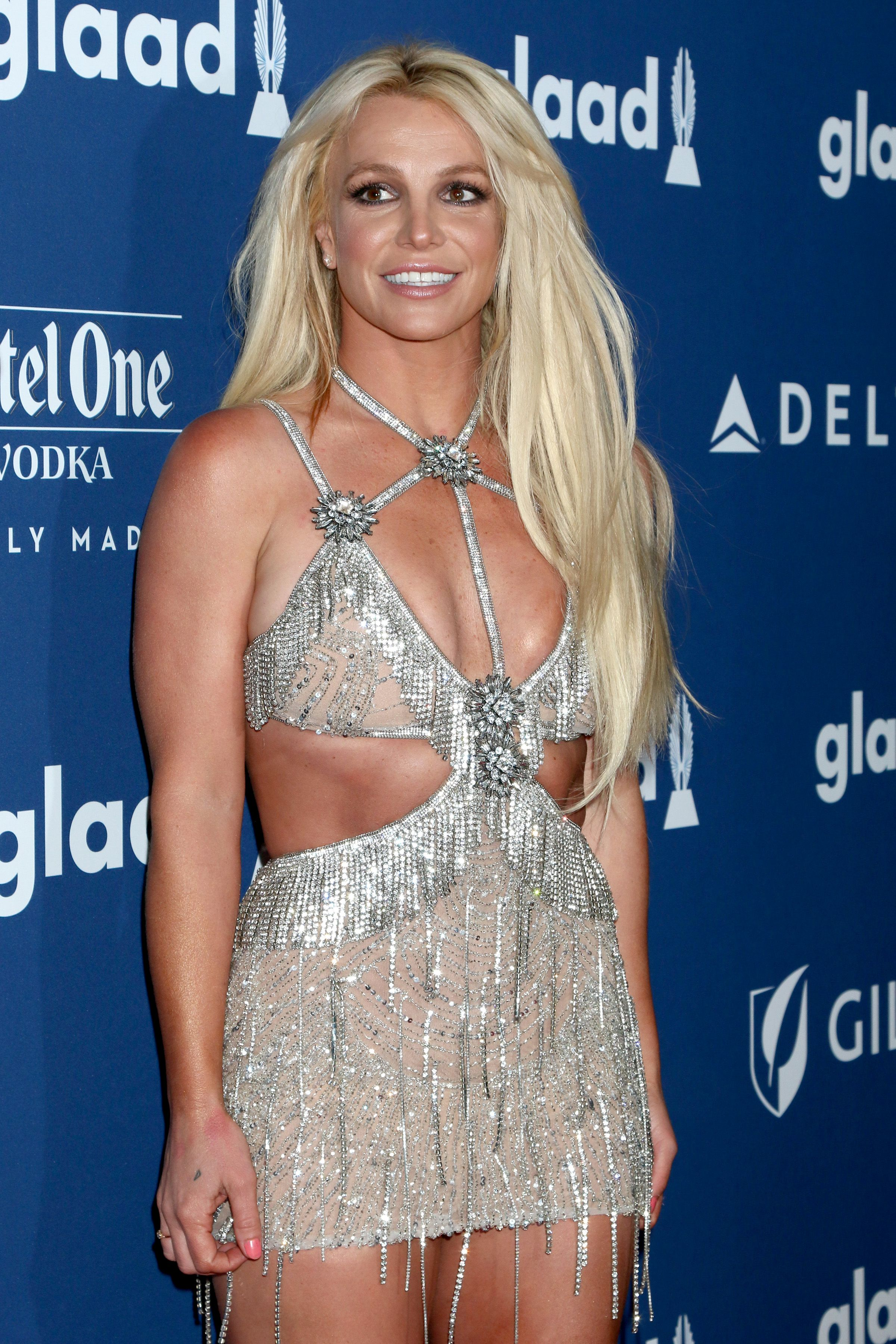 Britney Spears smiling in strappy silver dress