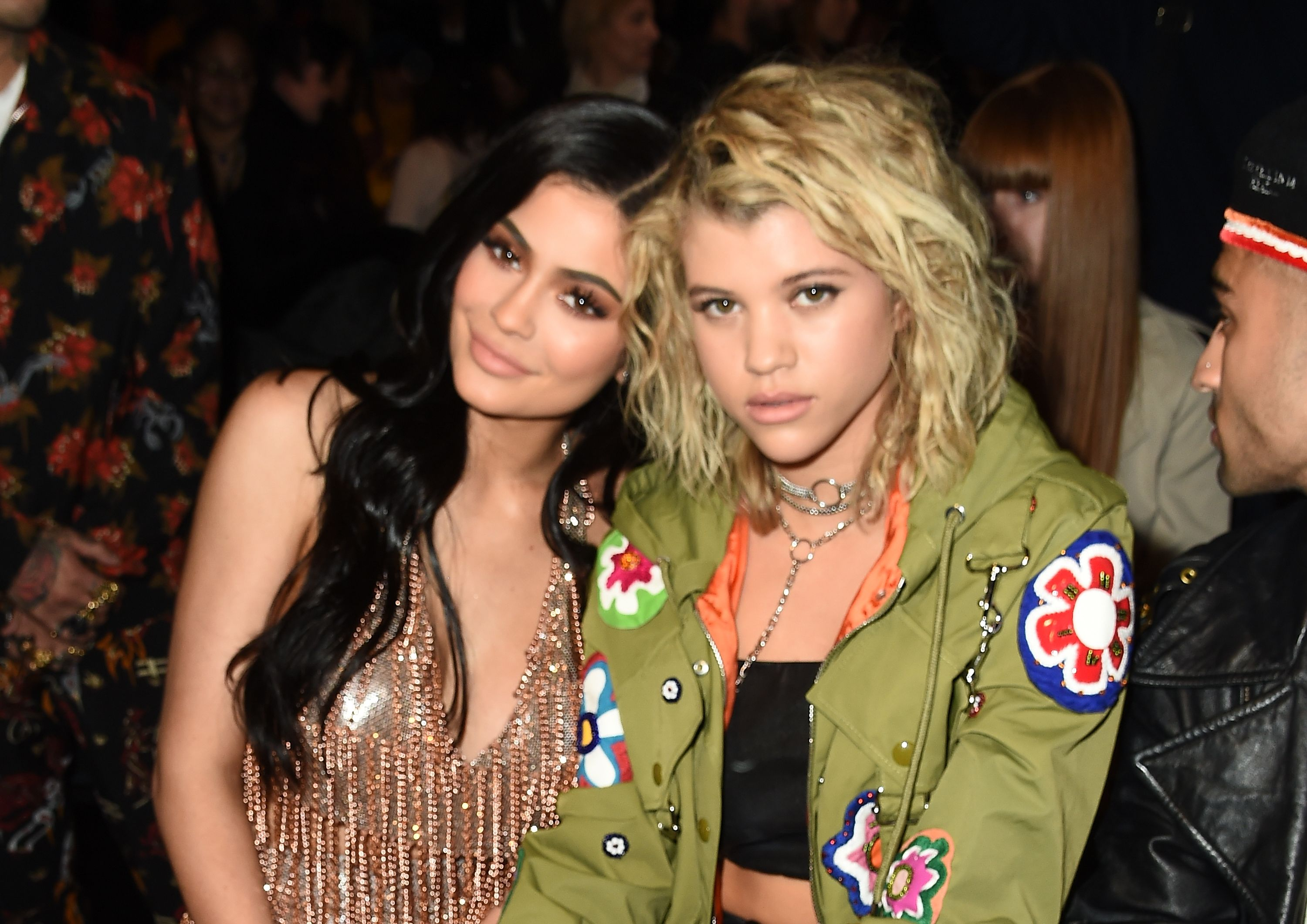 Kylie Jenner and Sofia Richie grinning, while sitting together.
