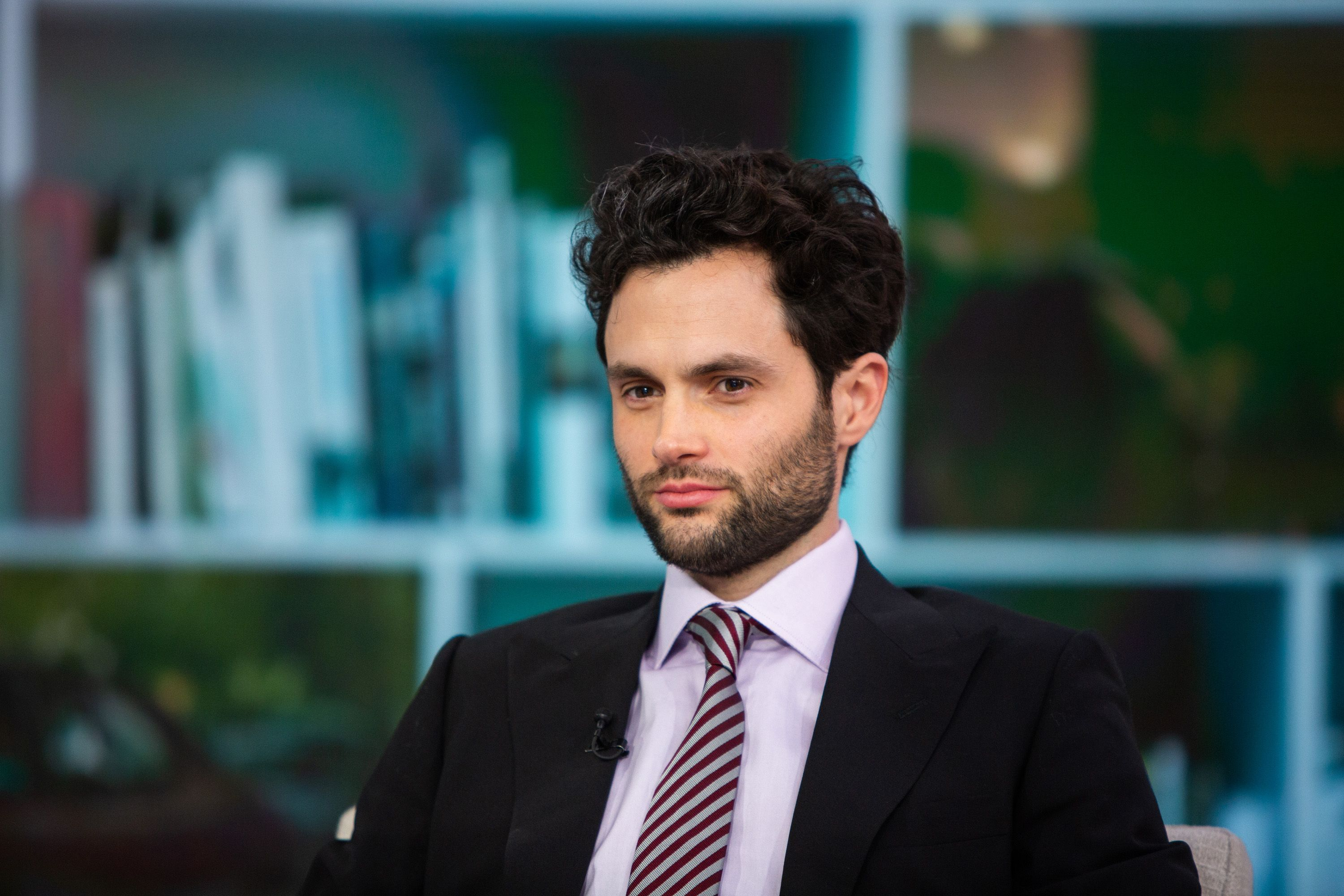 Penn Badgley looks amazing in black suit with lilac inner T-shirt and stripes tie to match.