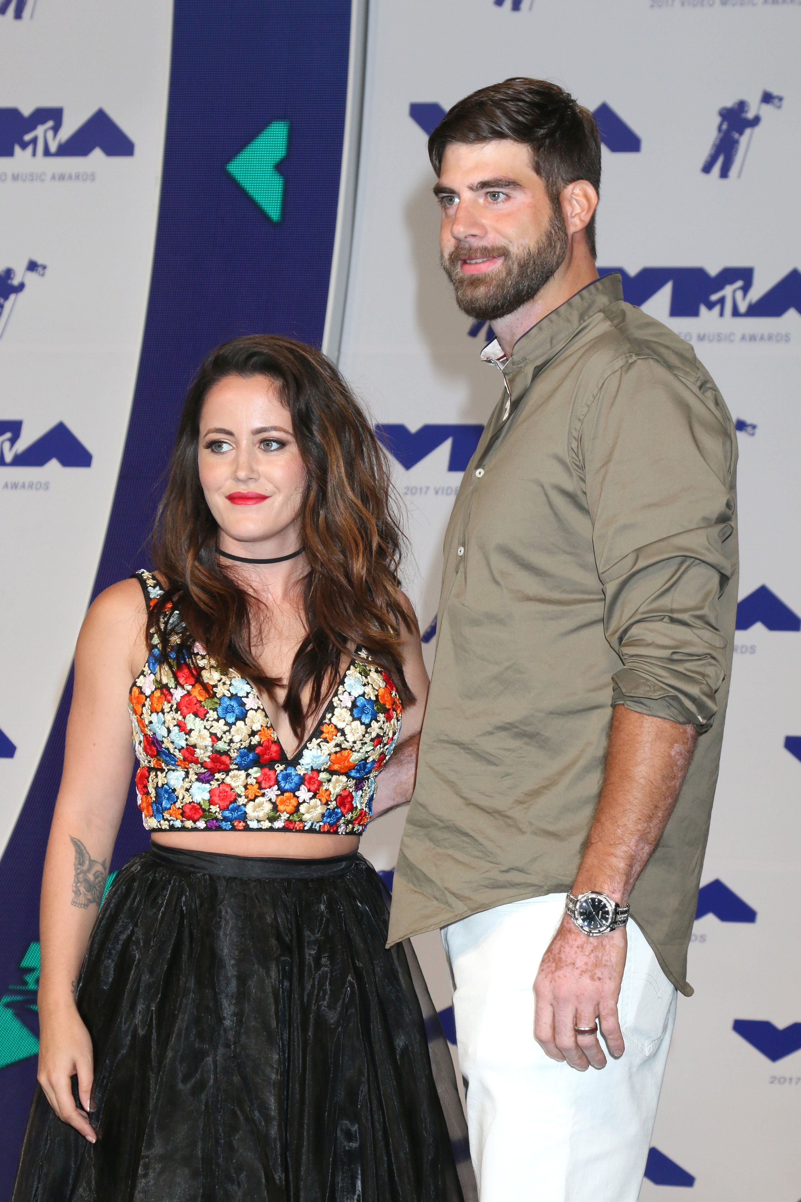 Jenelle Evans wears a floral crop top with David Eason in white pants.