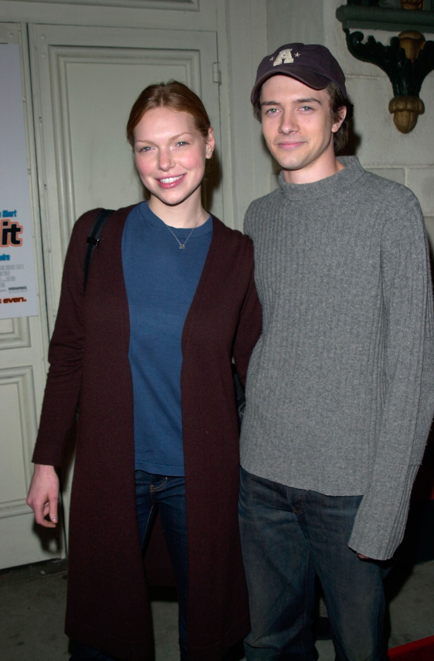 A young Laura Prepon and Topher Grace posing together.