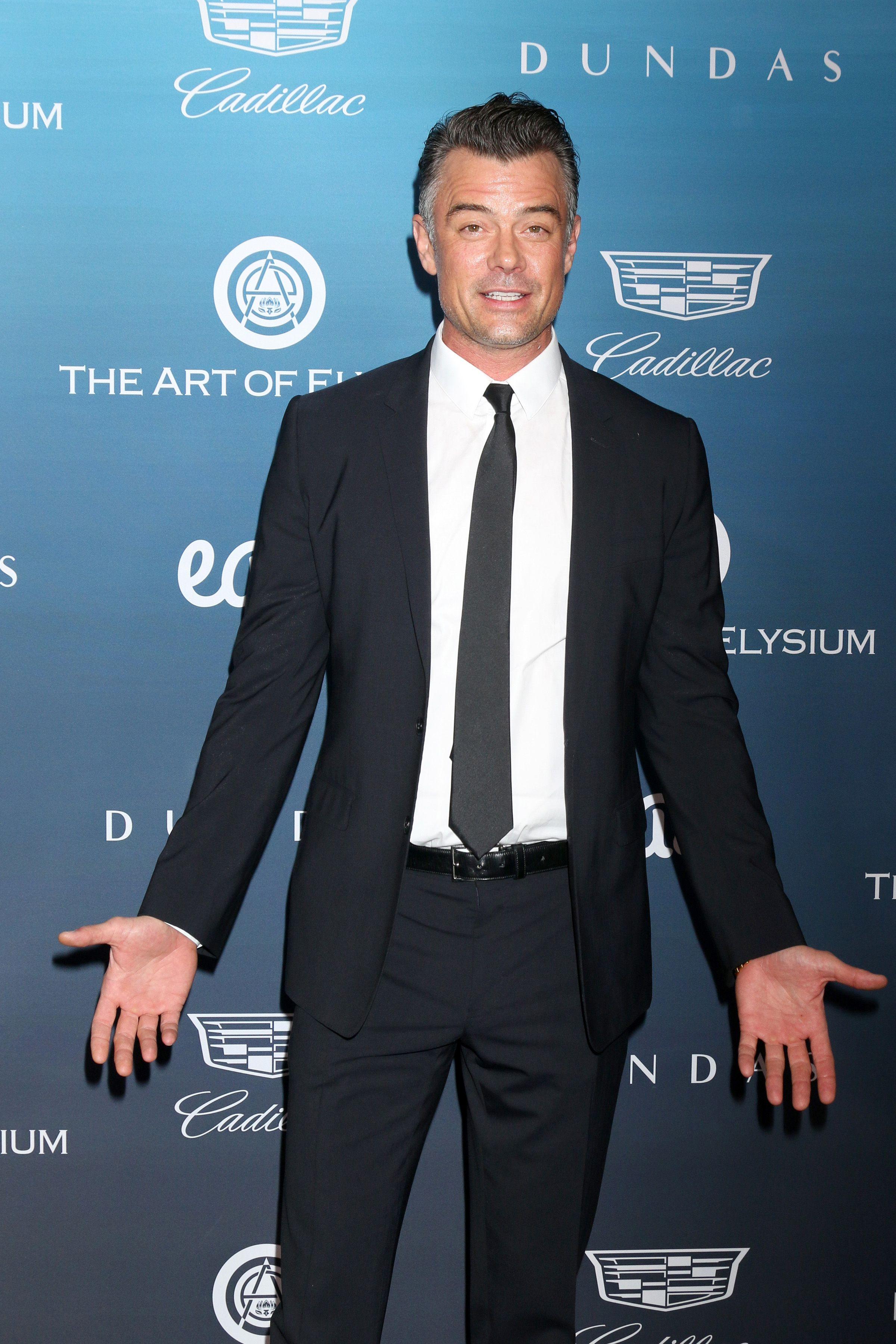 Josh Duhamel wears a black suit and tie.