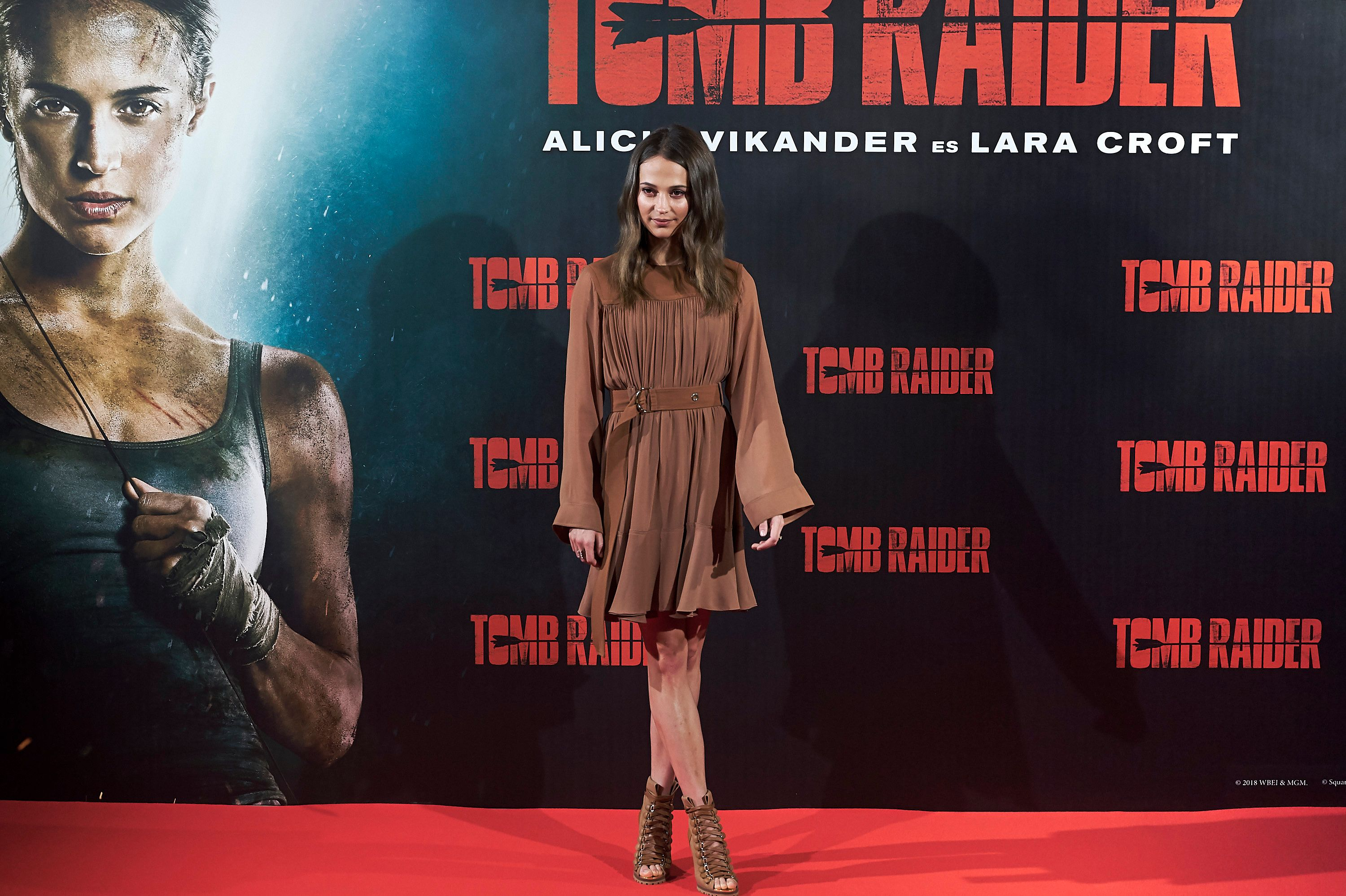 Alicia Vikander stands in a brown dress in front of a 'Tomb Raider' billboard.