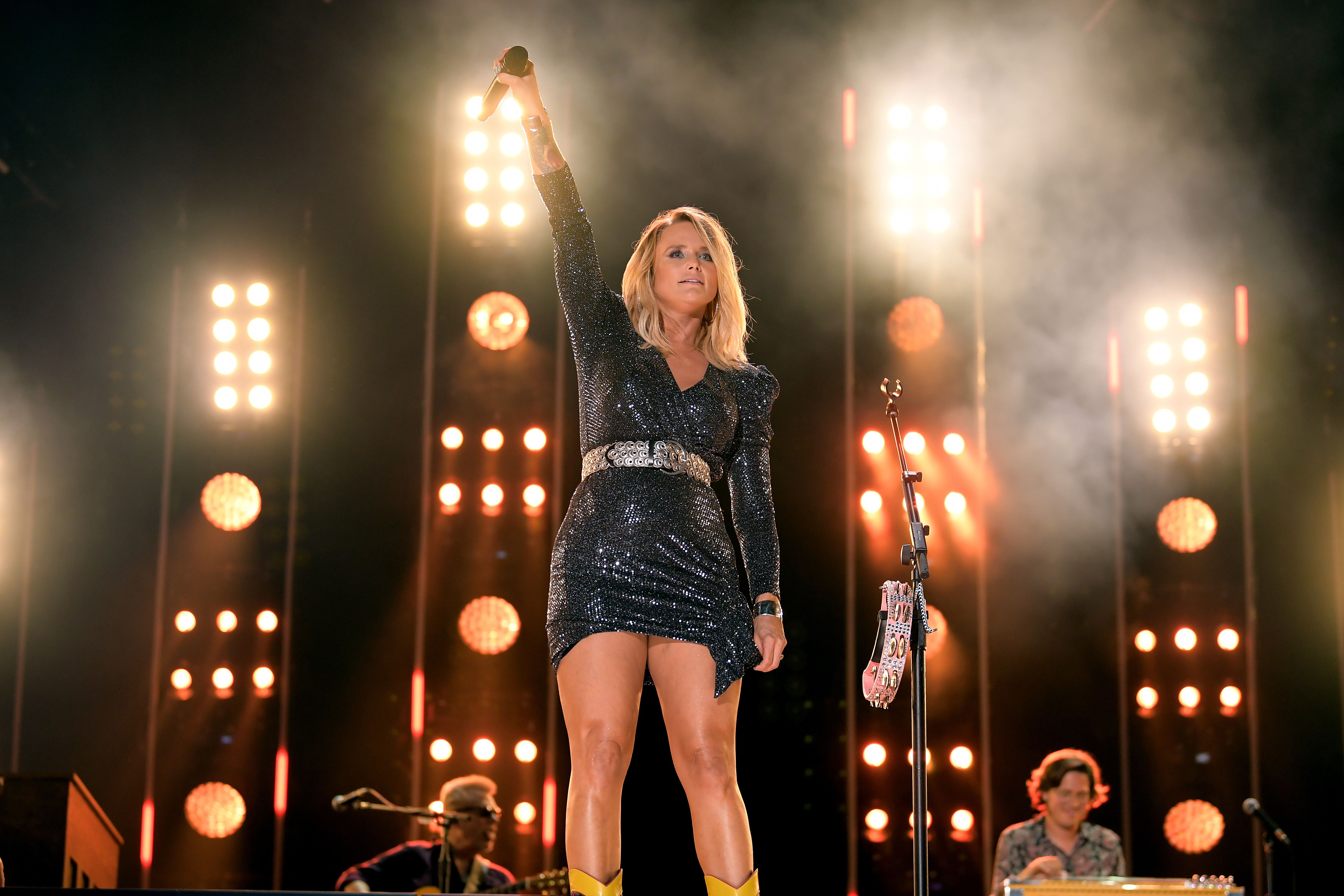 Miranda Lambert holding up a microphone on stage.