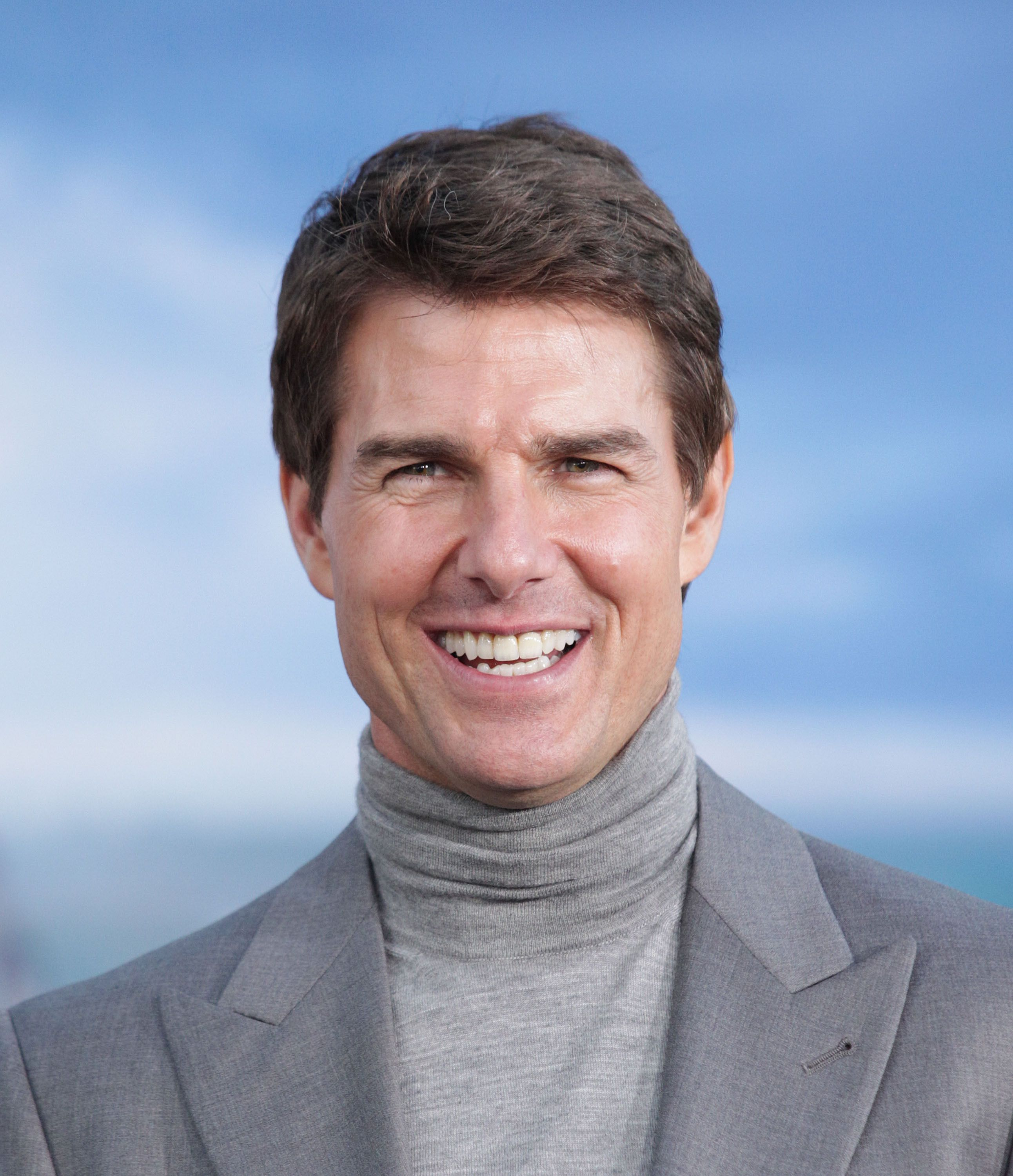 Close-up of Tom Cruise wearing a light-gray jacket and turtleneck.
