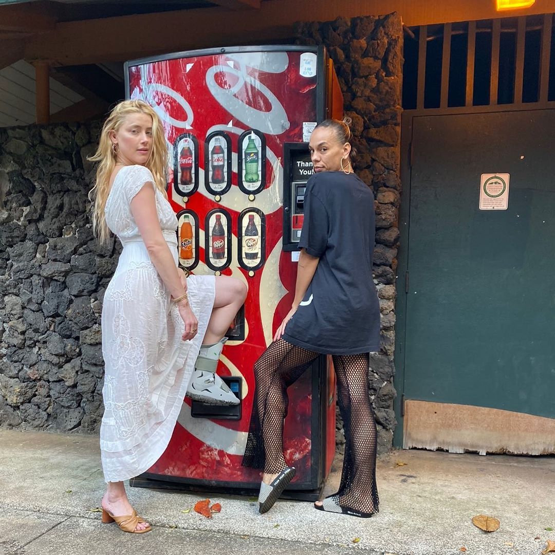 Amber Heard poses by a vending machine with a friend