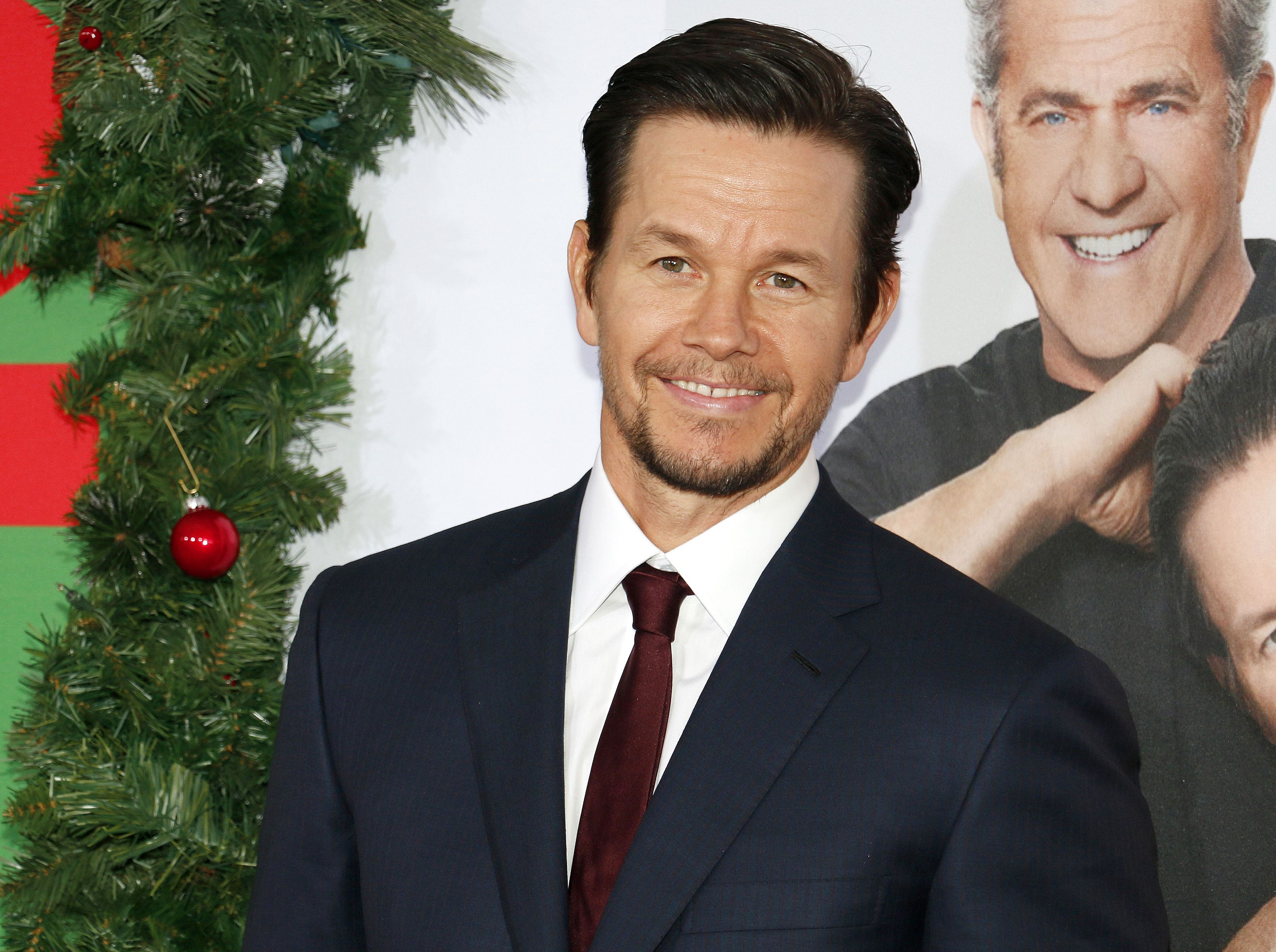 Mark Wahlberg wears a navy blazer and red tie.