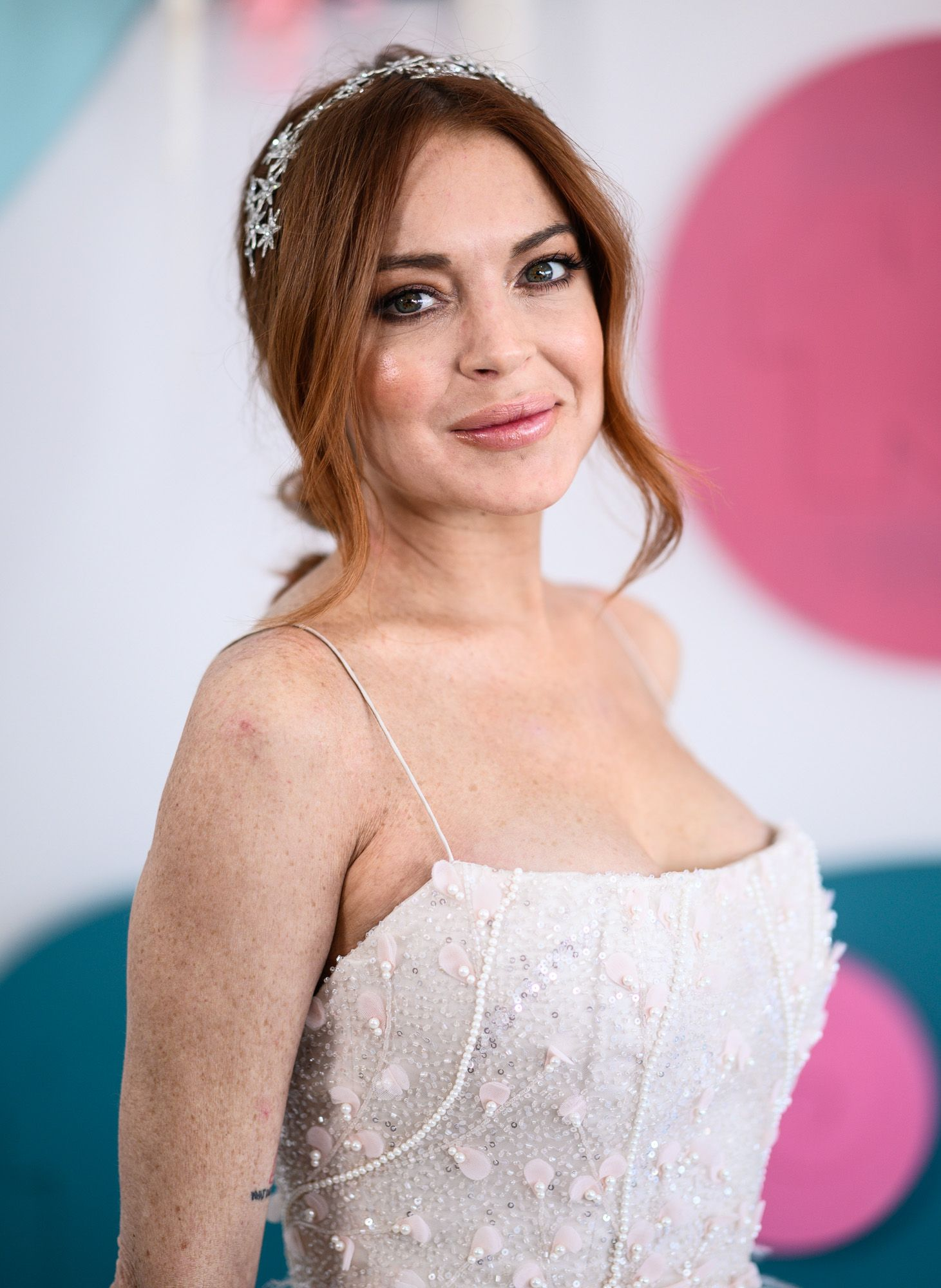 Lindsay Lohan looks captivating in this off-white dress with pink pearl designs.