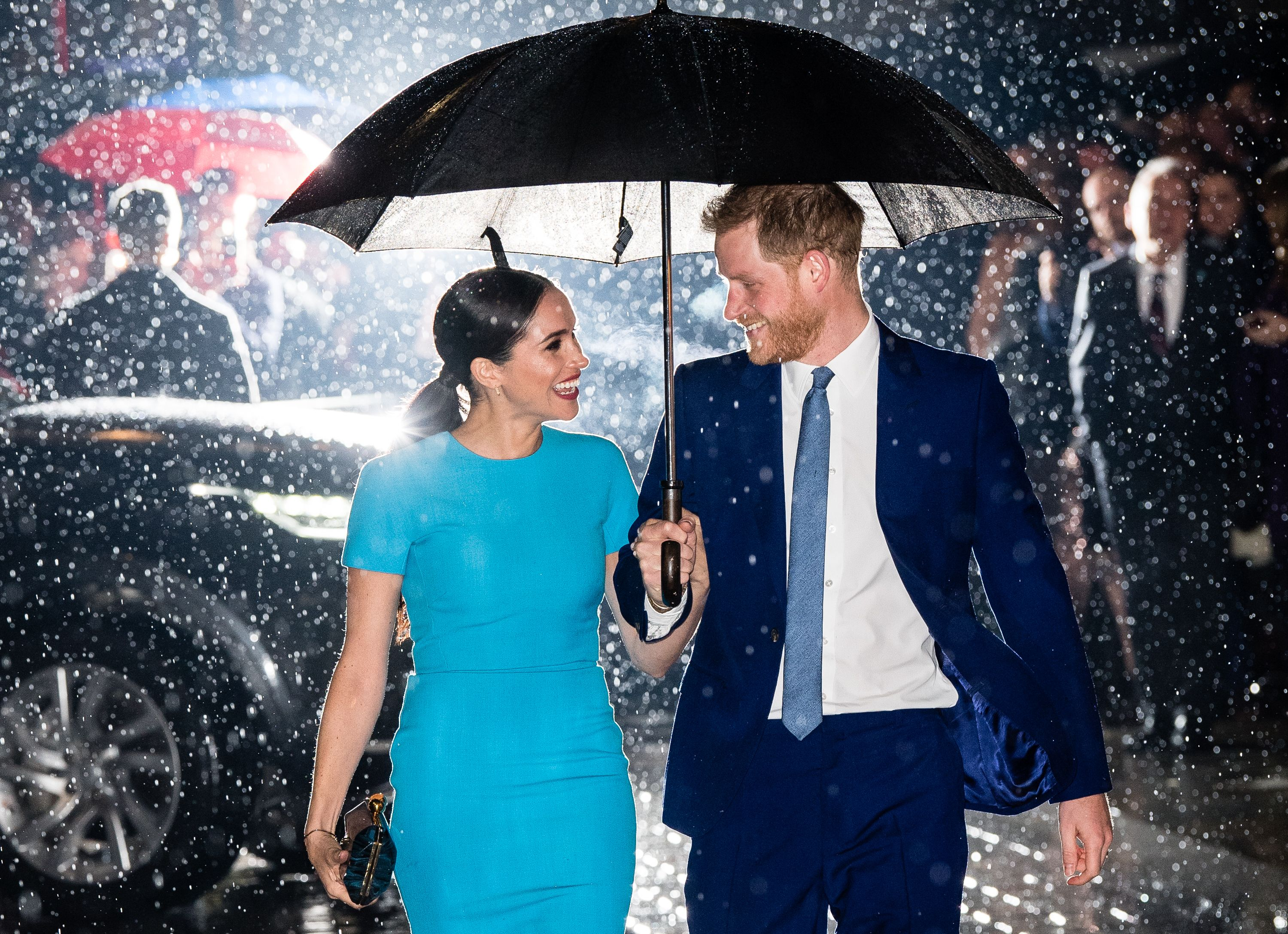 Meghan Markle and Prince Harry smile at each other under an umbrella in the rain