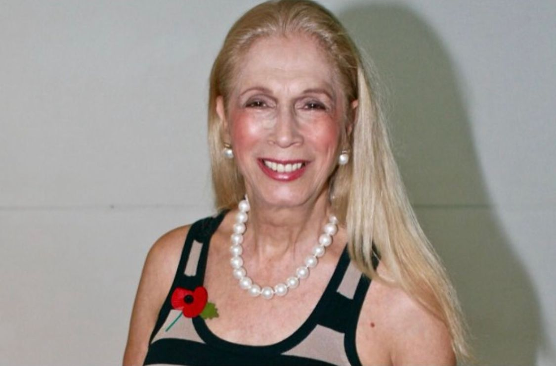 A photo showing Colin Campbell sporting a sleeveless blouse with white coral beads around her neck.