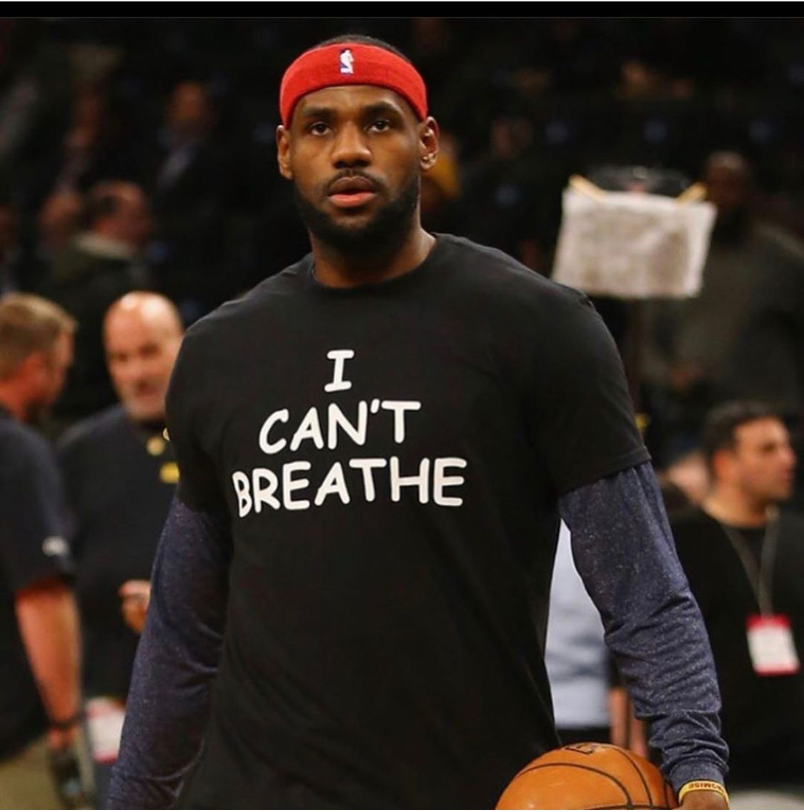 A photo showing LeBron James wearing a black shirt on a long sleeve sweat shirt and a basketball on his left hand.