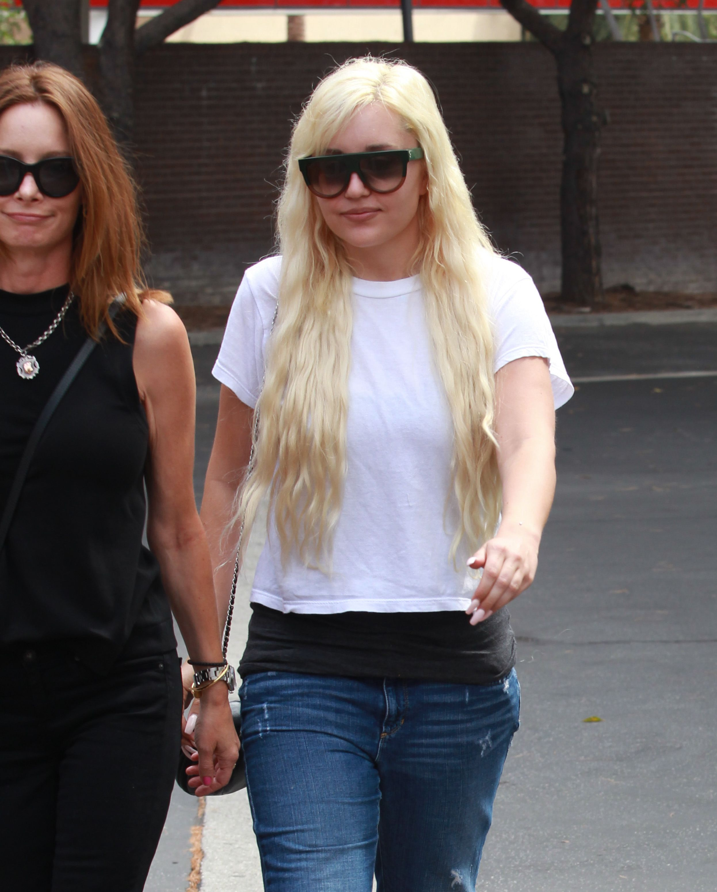 Amanda Bynes walks down the street with sunglasses on
