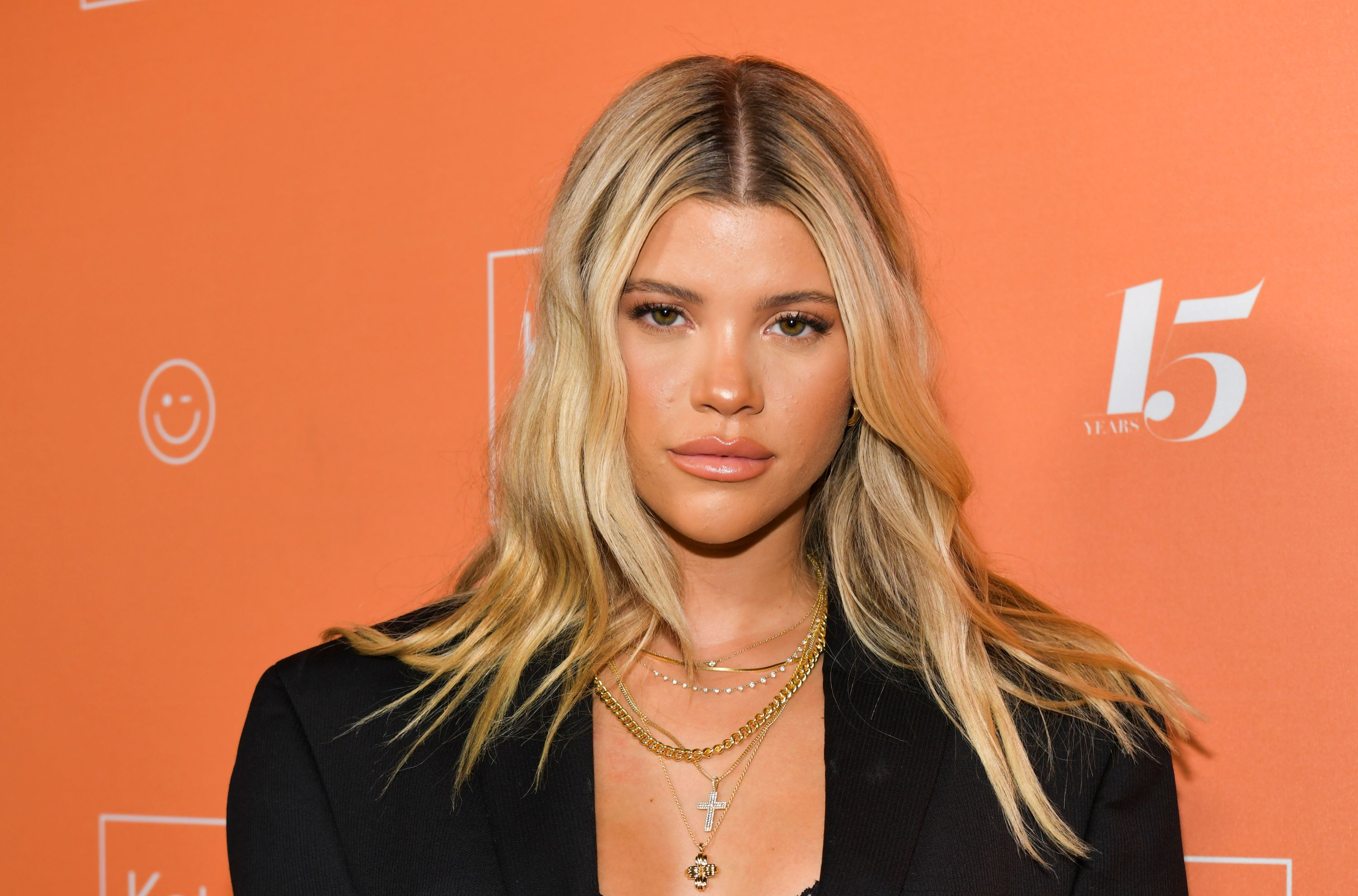 Sofia Richie posing while at an event with orange backdrop.