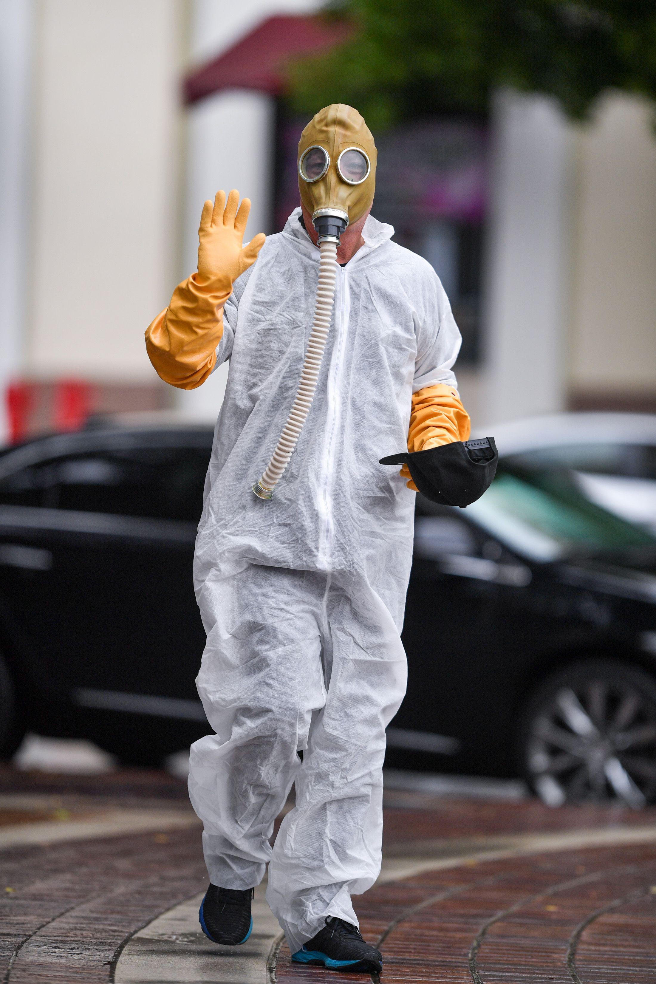 Howie Mandel walks down the street wearing a hazmat suit