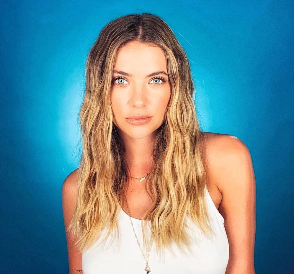 Ashley Benson posing in front of a blue background.