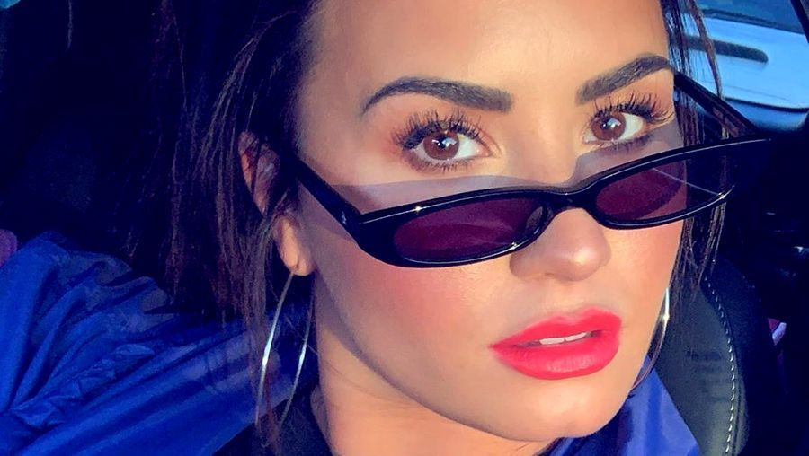 Demi Lovato wearing small sunglasses and a red lip