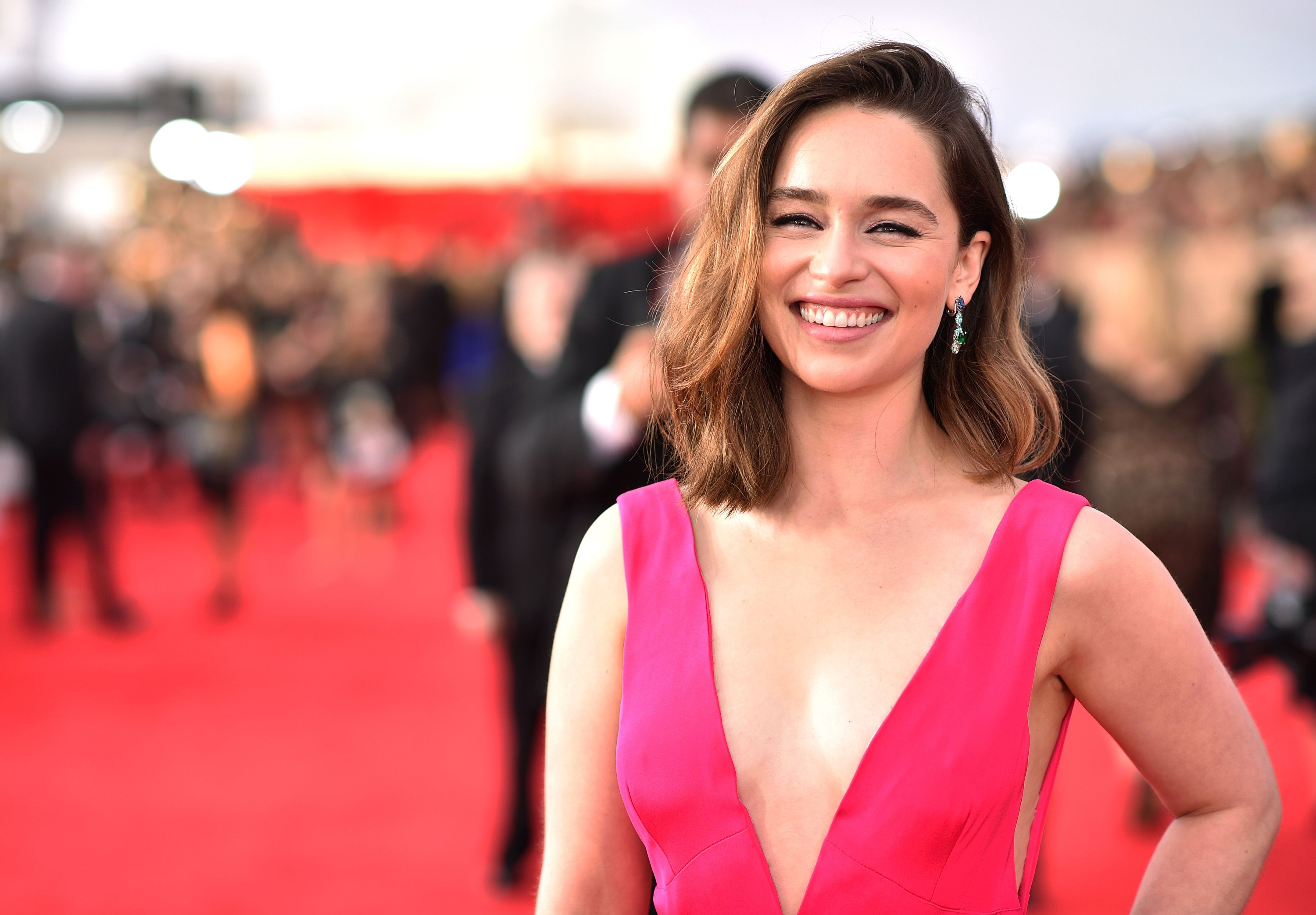 Emilia Clarke wears a low cut pink gown with her hair down.