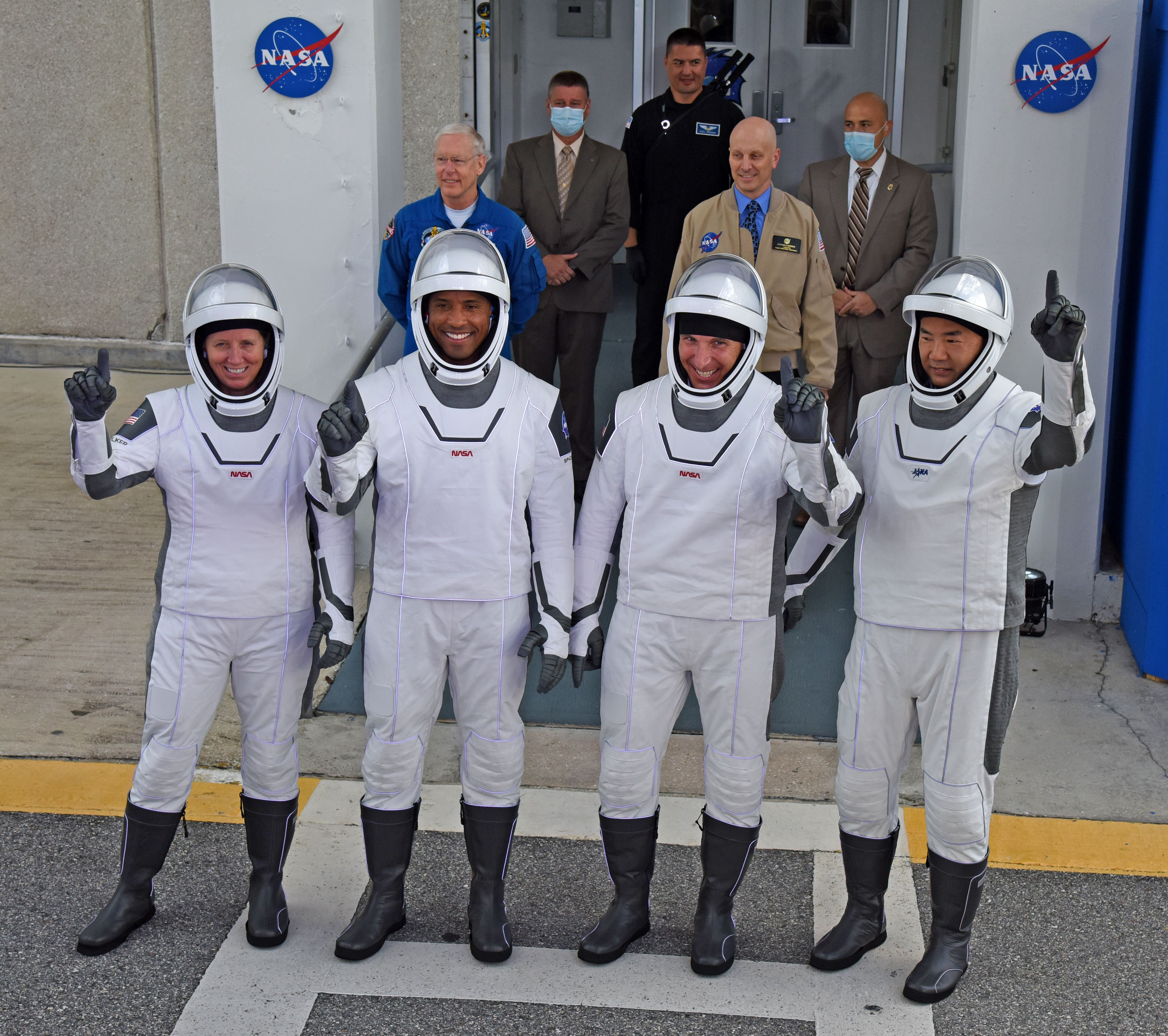SpaceX astronauts pointing to the sky.