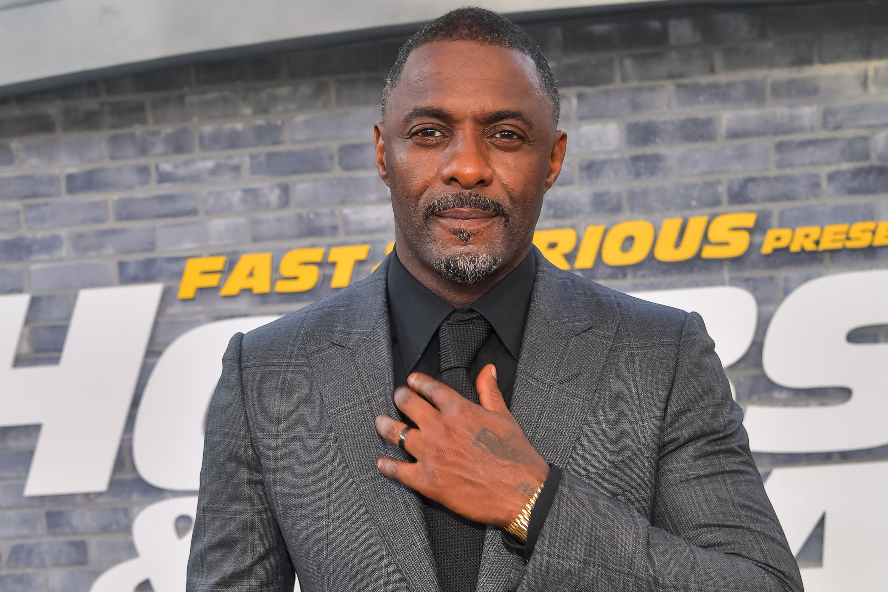 Idris Elba poses in front of a Fast & Furious sign
