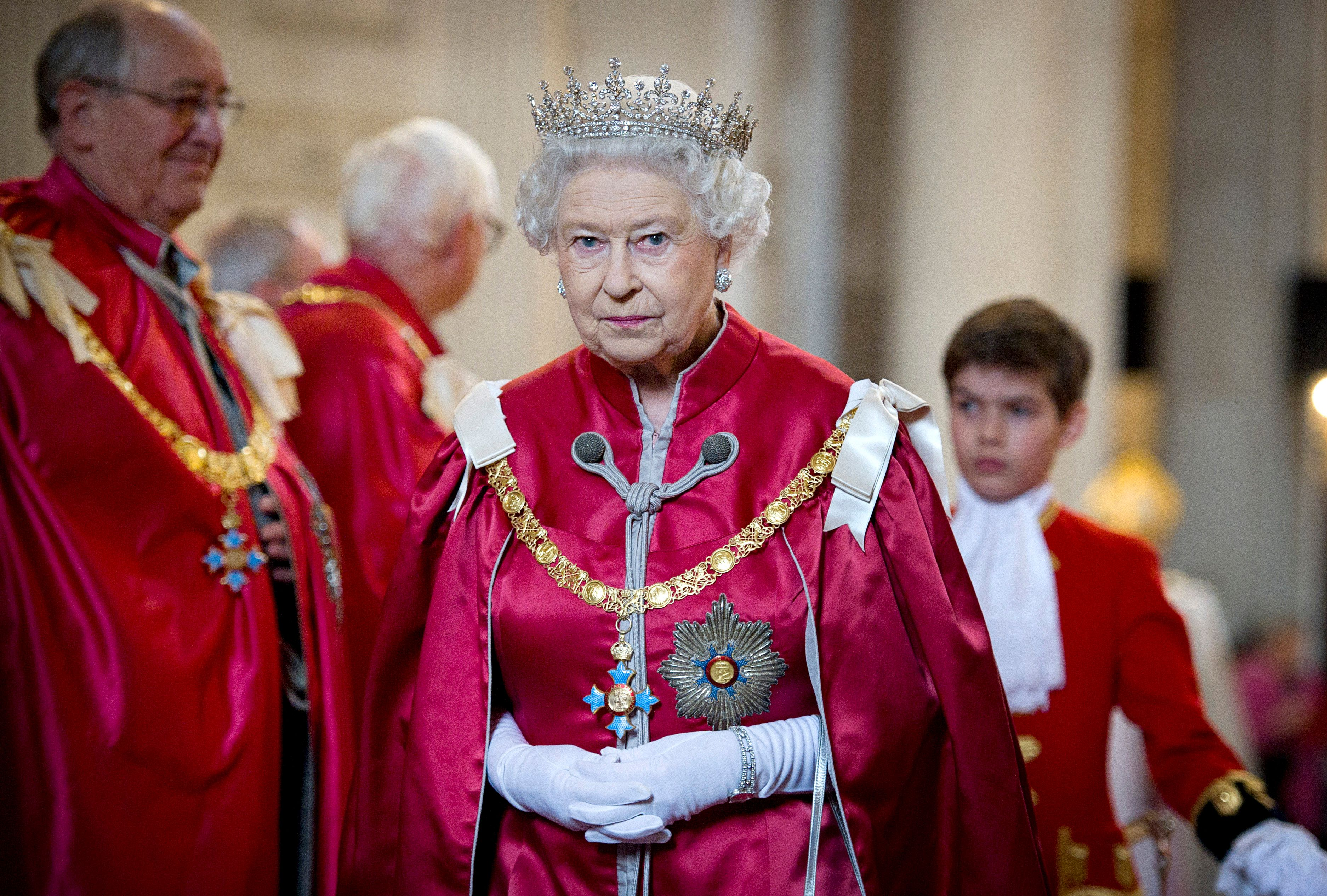 Queen Elizabeth stands clasping her hands wearing all red