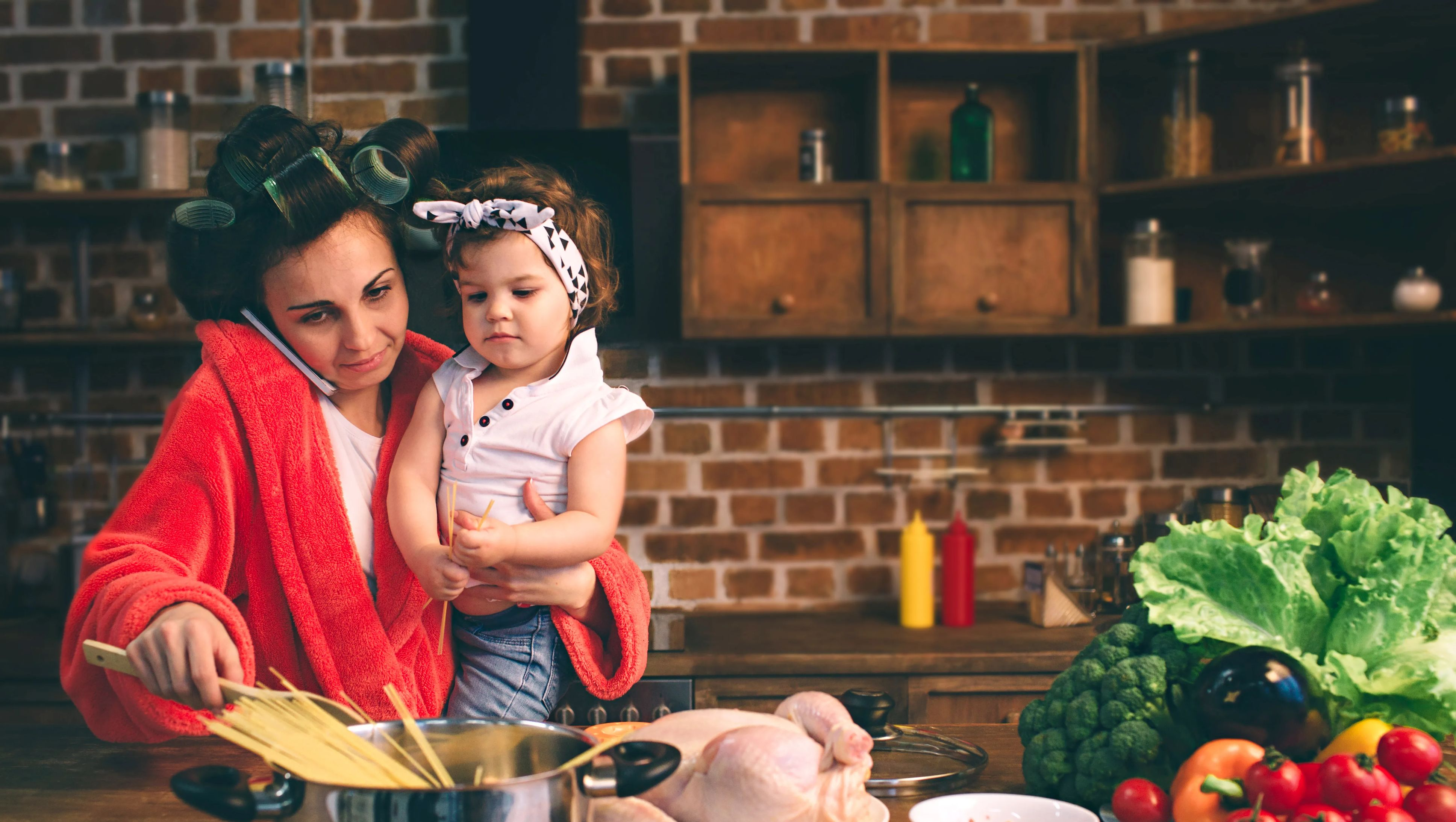 Busy mom cooking dinner while holding a baby