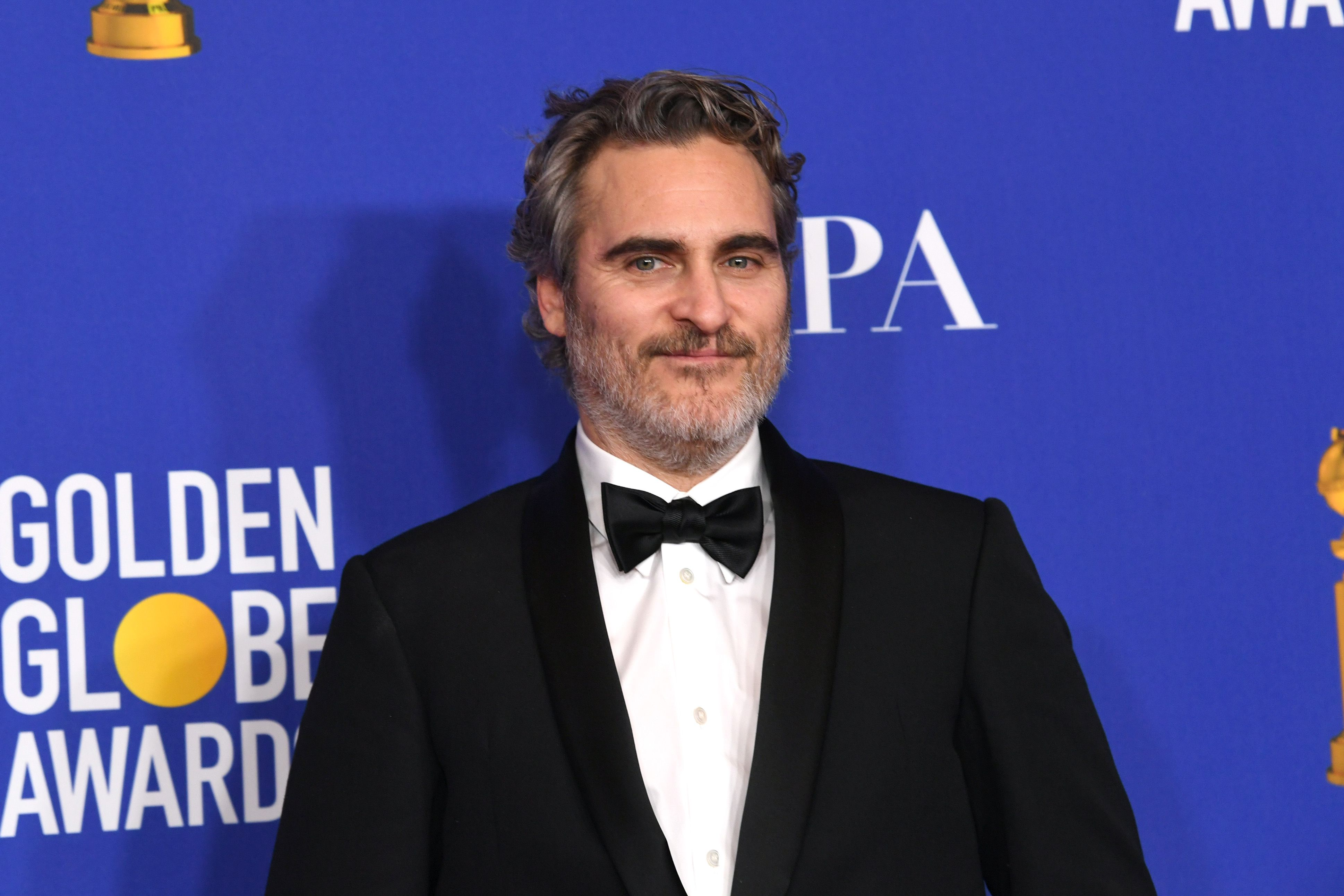 Joaquin Phoenix looks amazing in black suit and white inner T-shirt with a quirky smile on his face