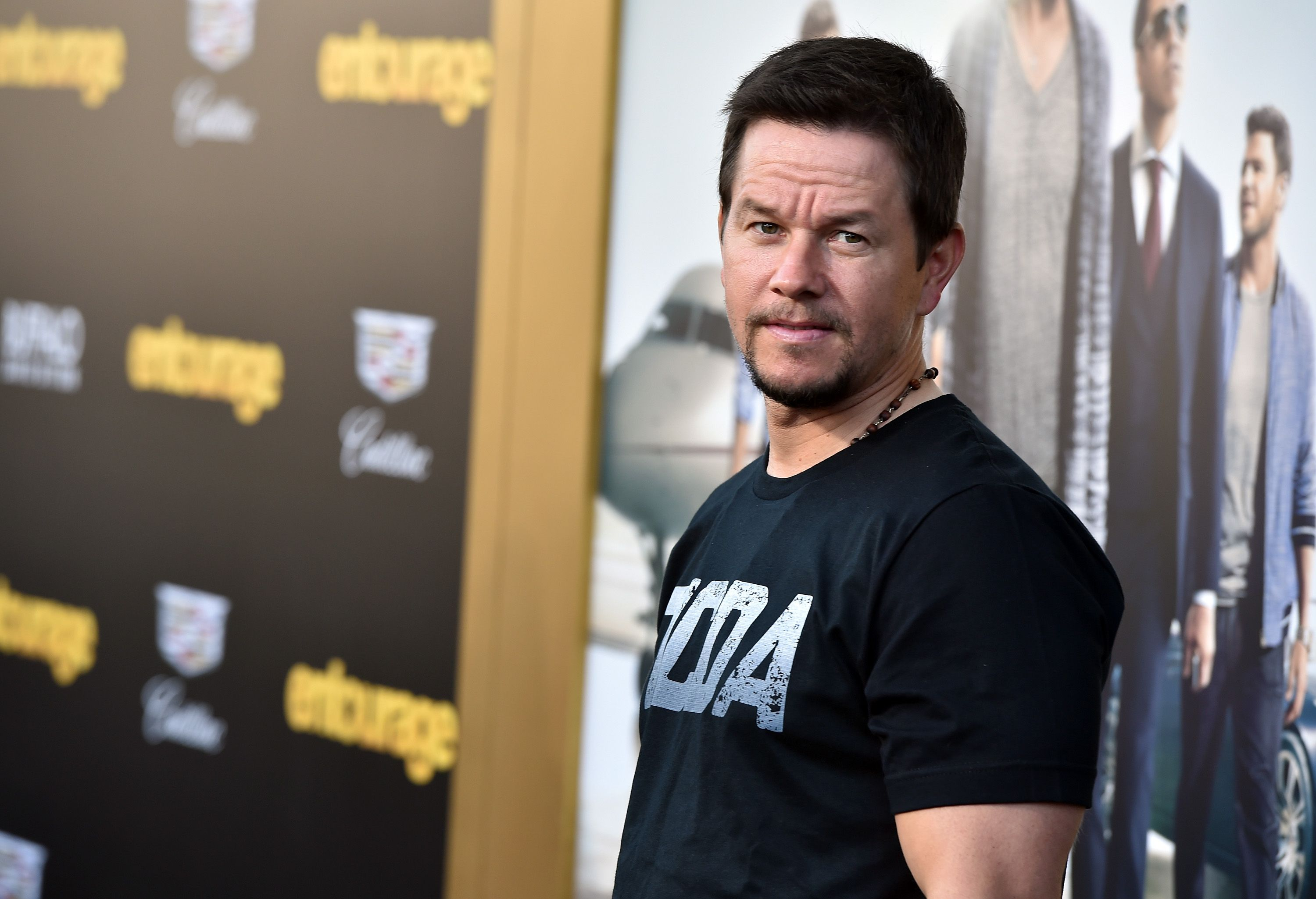 Mark Wahlberg wears a black T-shirt and beaded necklace.
