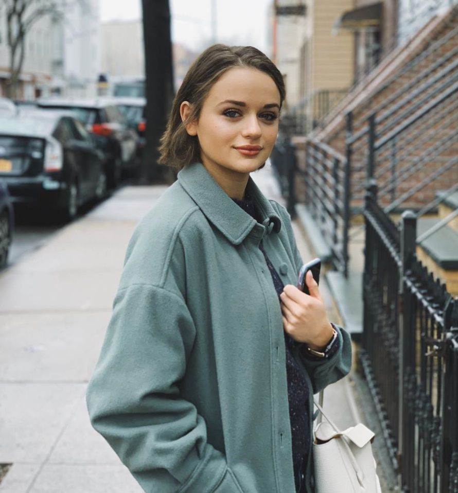 Joey King standing outside wearing a green coat.