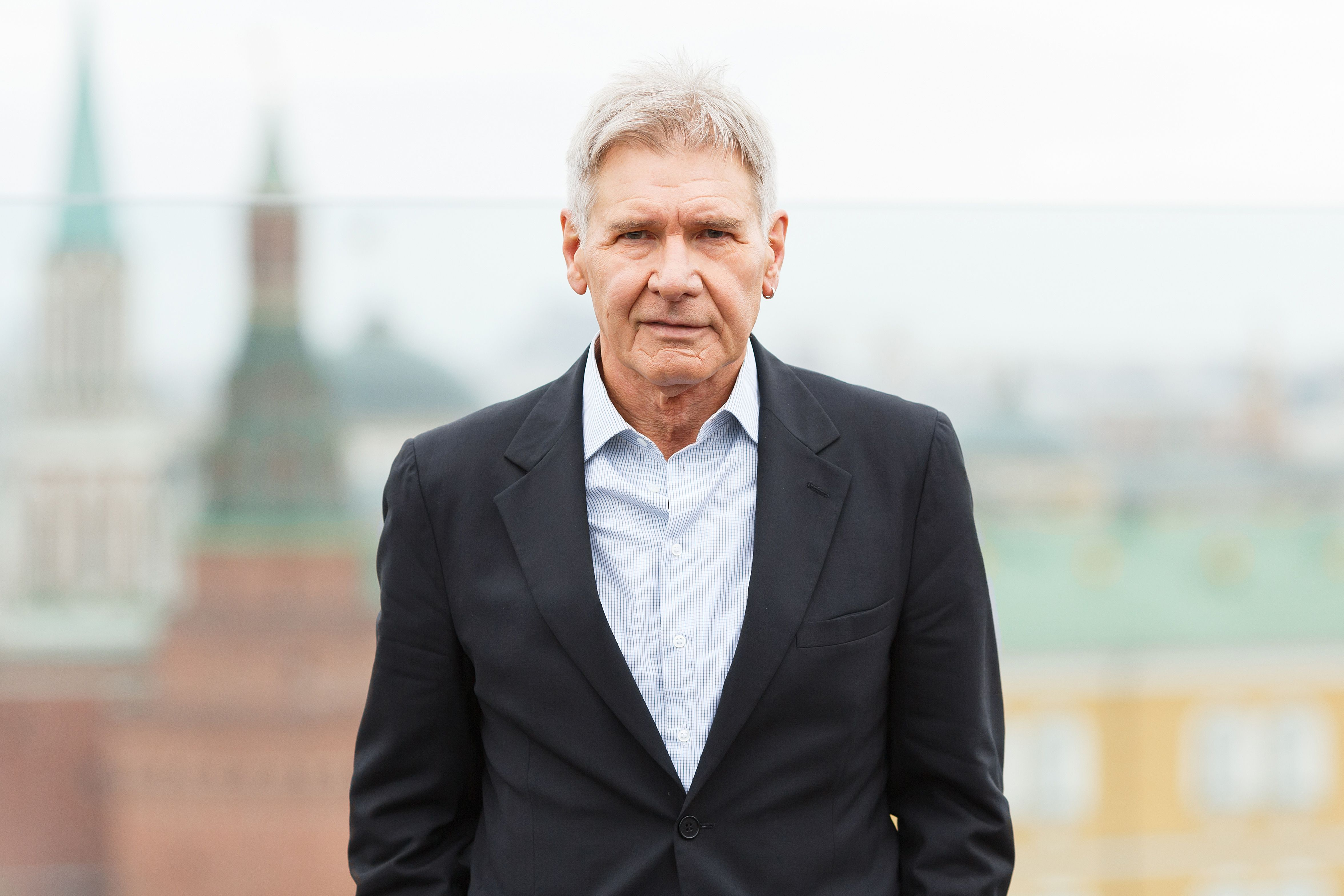 Harrison Ford wears a black blazer and white button-up.