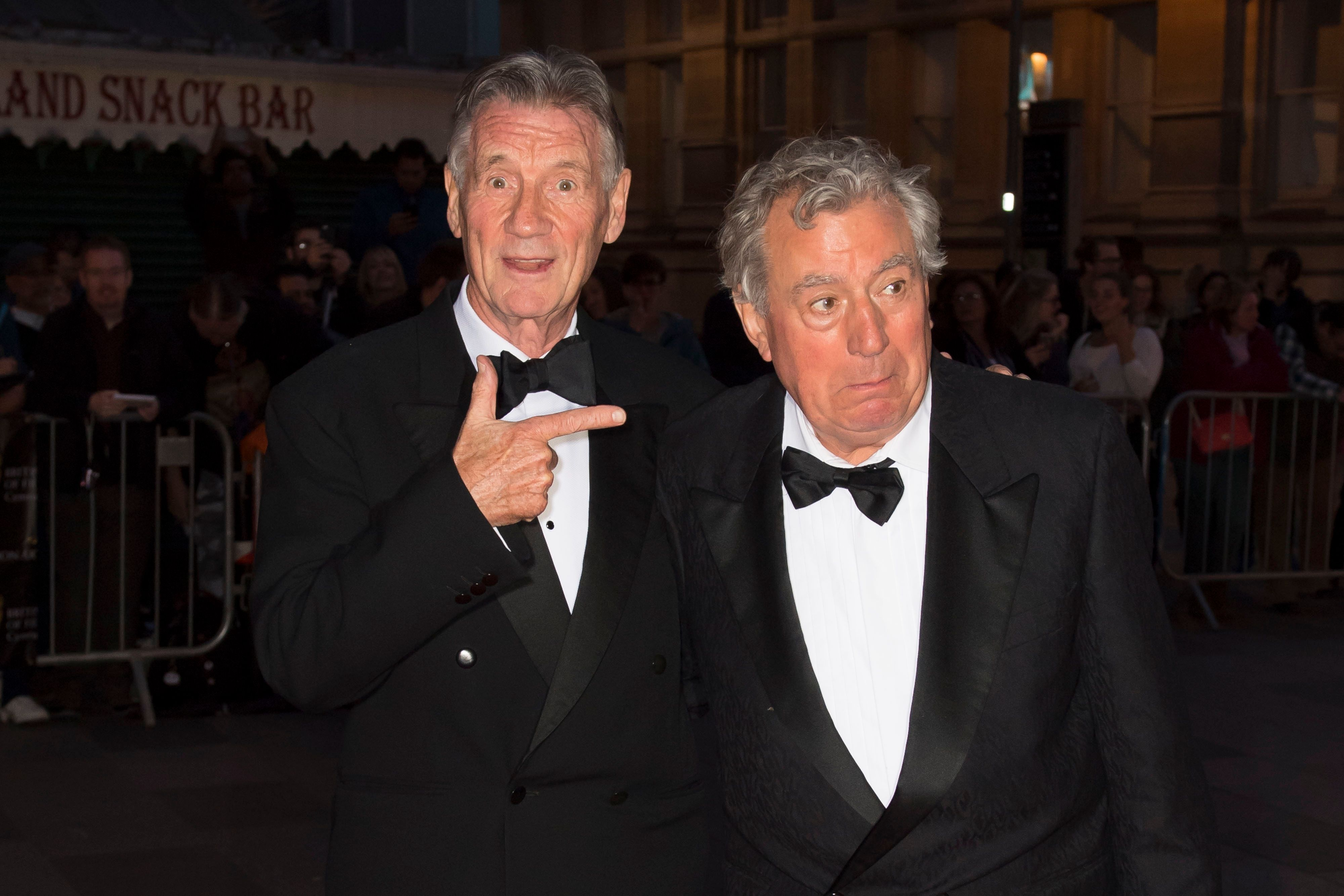 Michael Palin (left) points at Terry Jones (right)