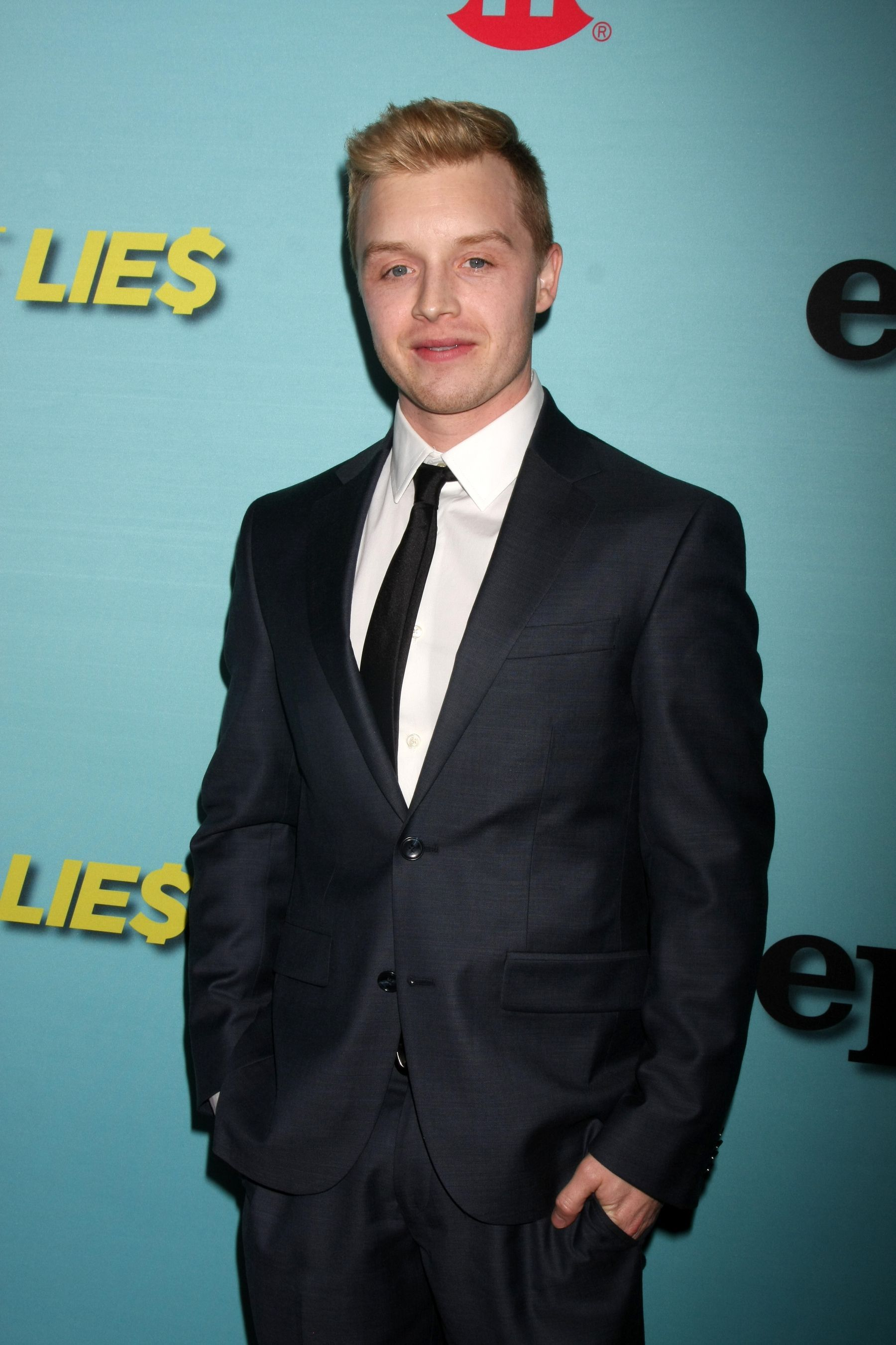 Noel Fisher in a suit with blonde hair.