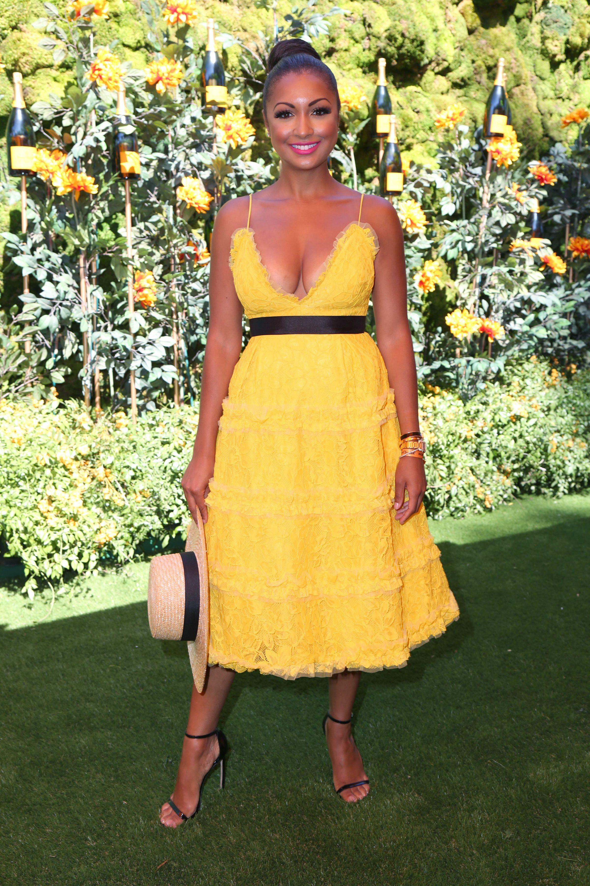 Eboni K. Williams wears a yellow dress and black belt.