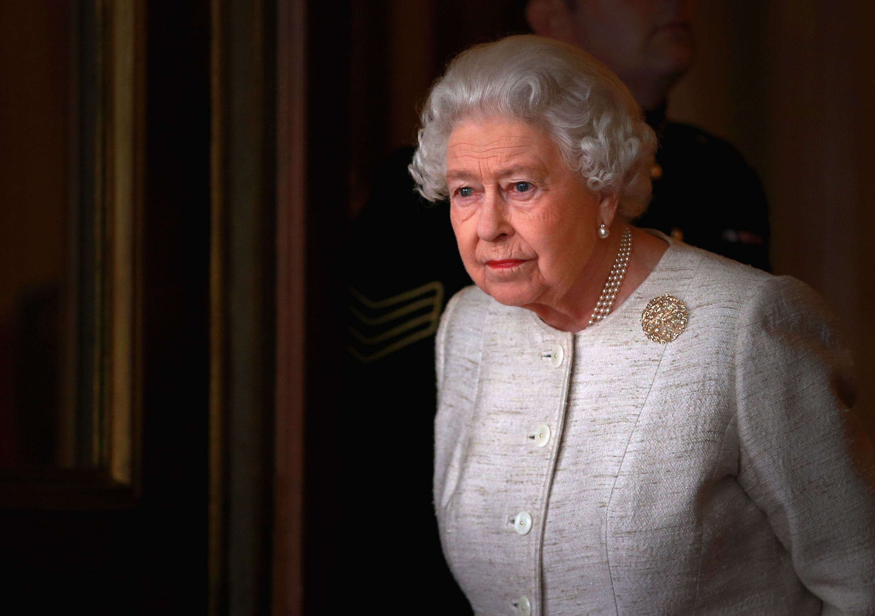 Queen Elizabeth II looking pensive in a white jacket