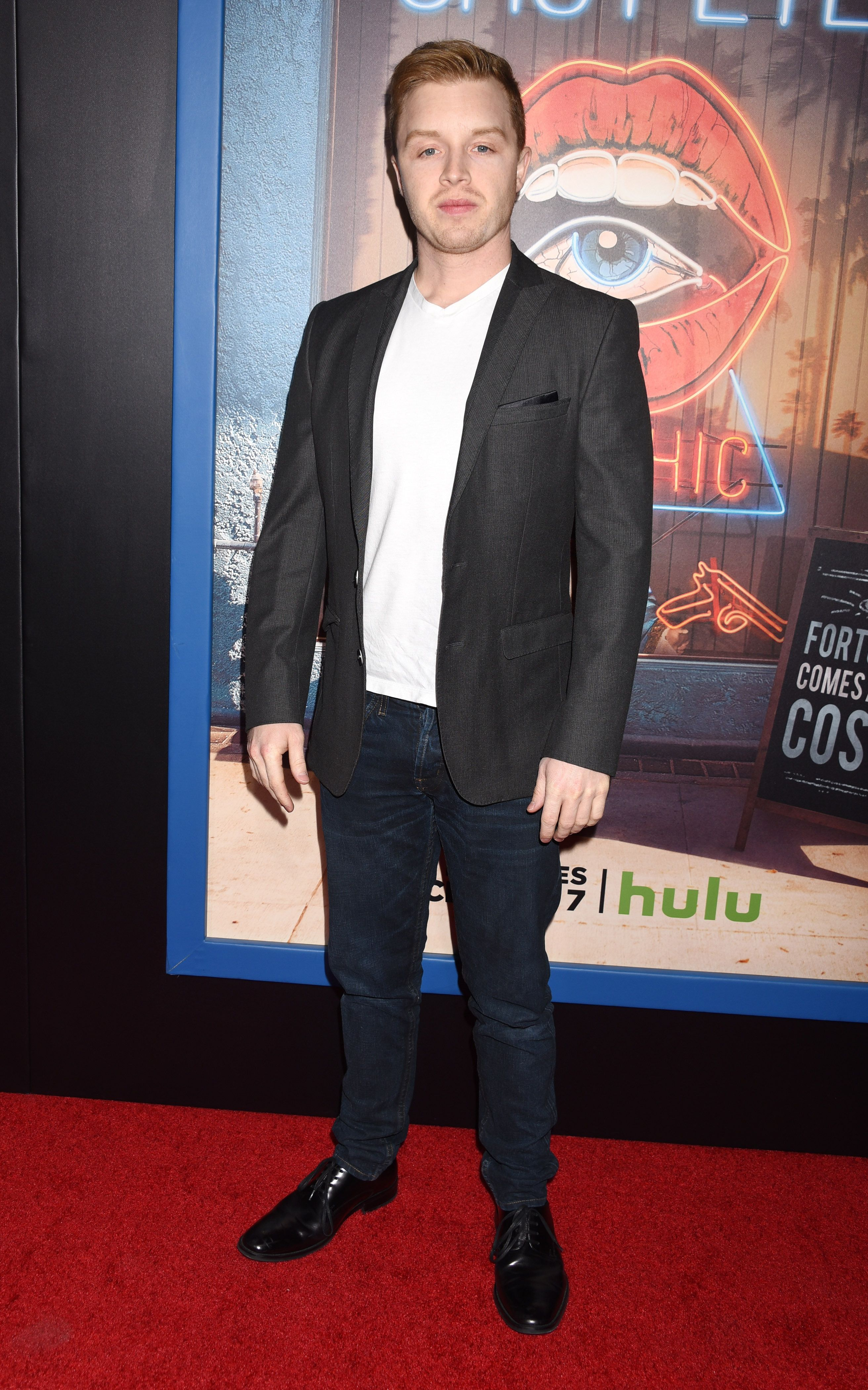 Noel Fisher wears jeans on red carpet with show poster in background.