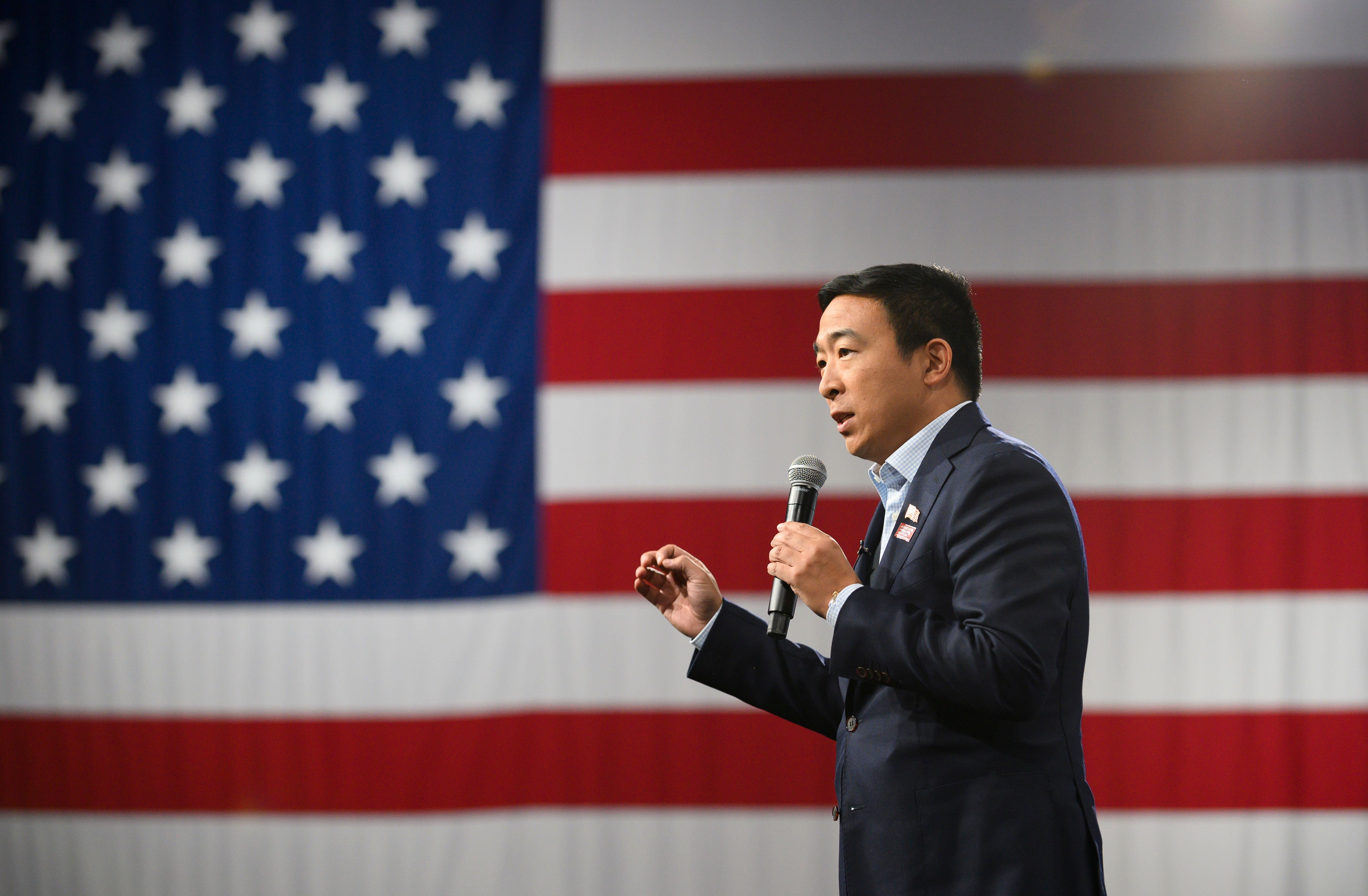 Andrew Yang speaking in front of an American flag
