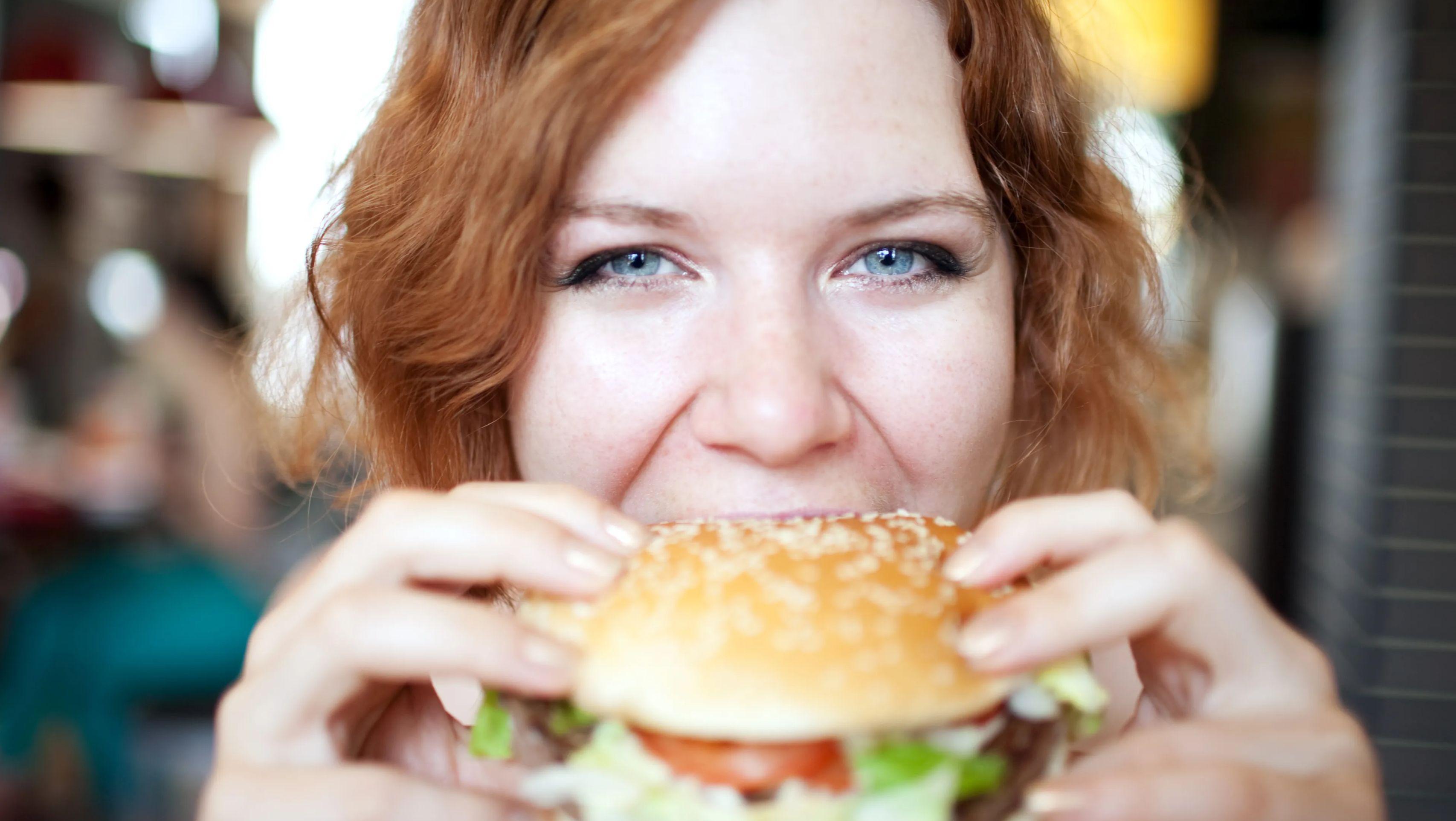 A woman eating a hamburger.