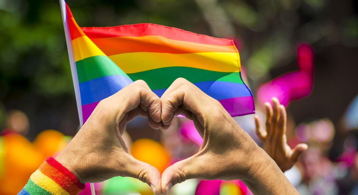 LGBTQ rights protesters waive rainbow flags.