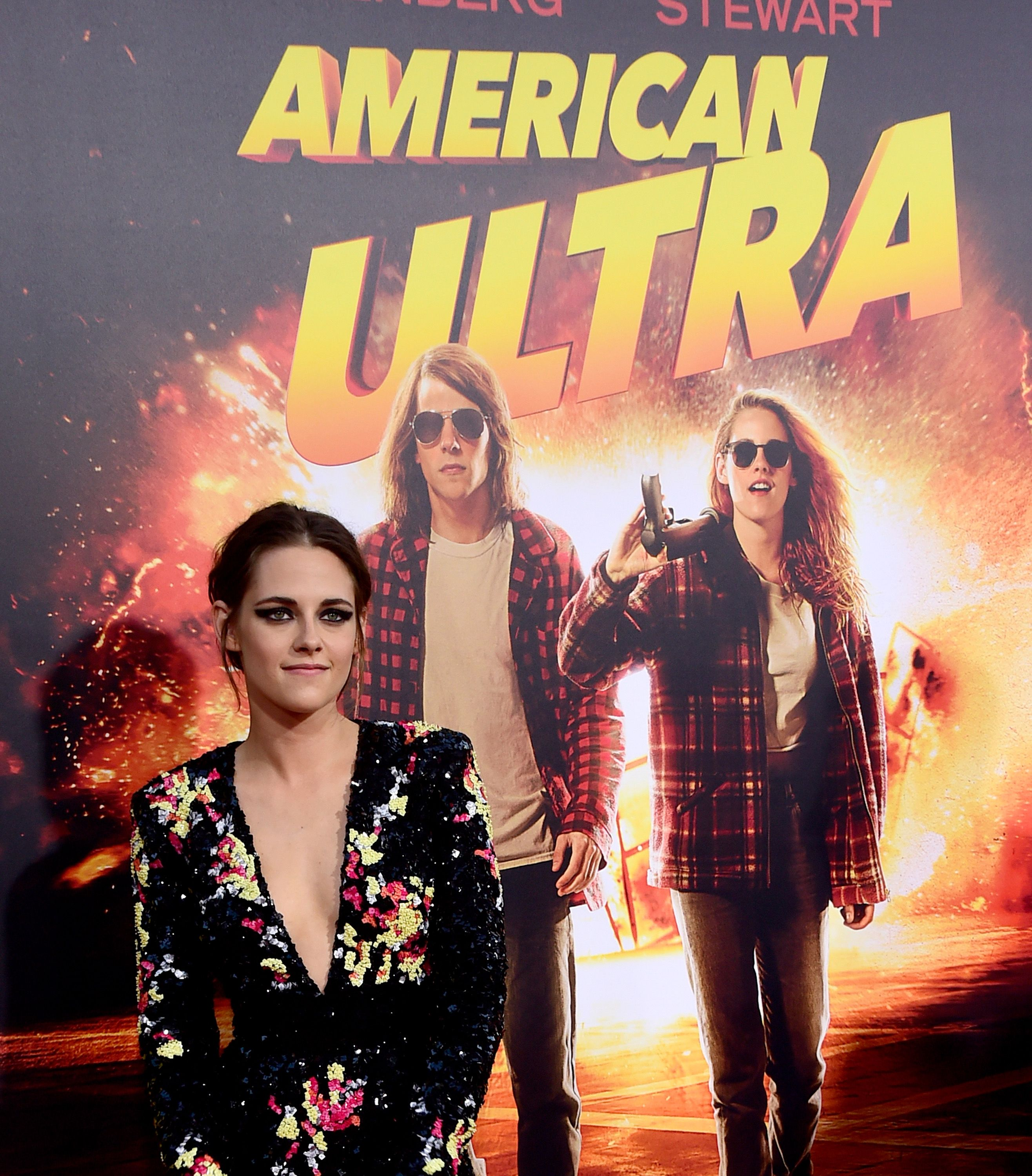 Kristen Stewart stands in front of an 'American Ultra' movie poster.